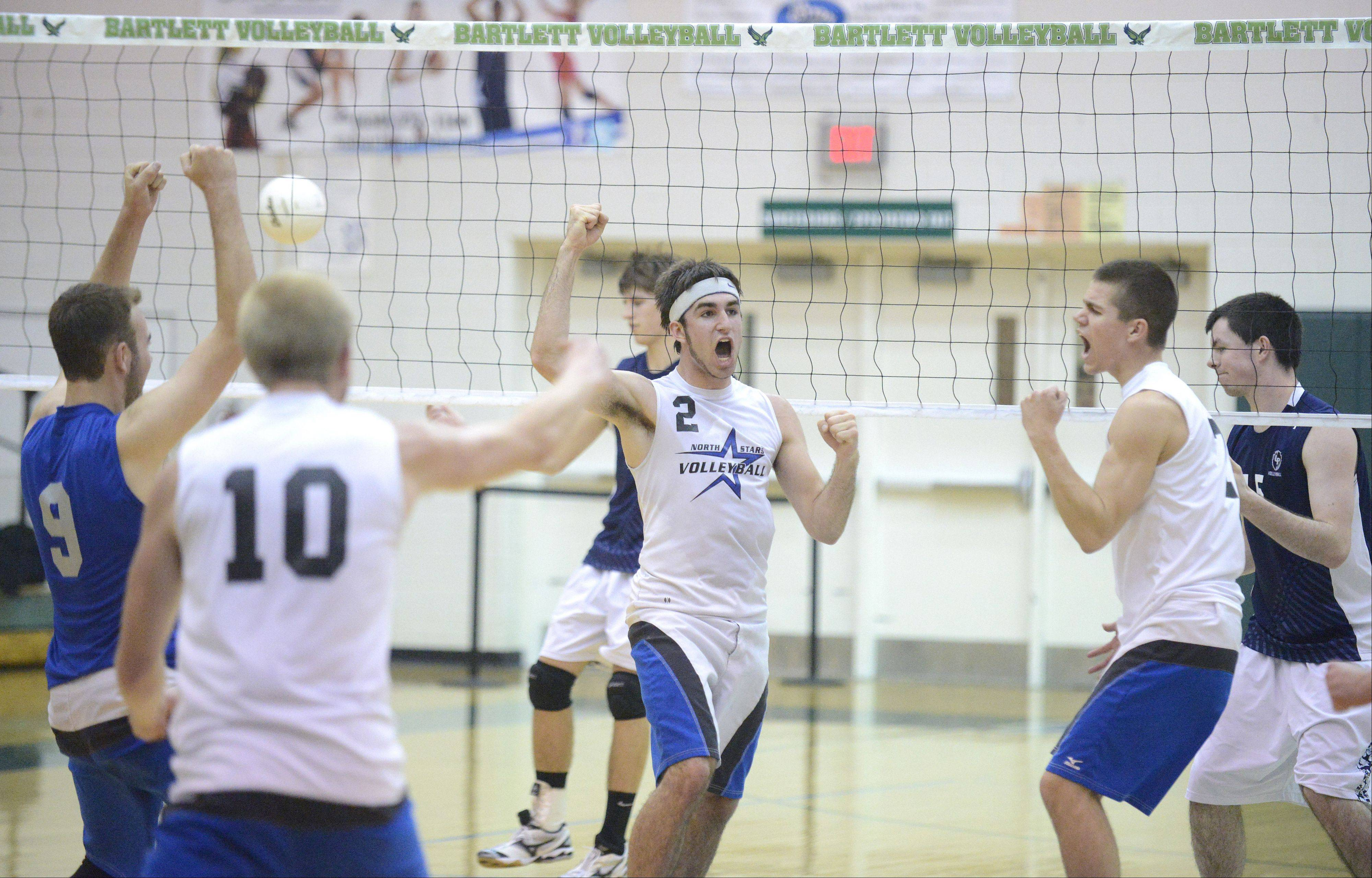 St. Charles North's Jonathan Orech, center, and teammates celebrate a point in the second game of sectional championship play against Lake Park in Bartlett on Tuesday.