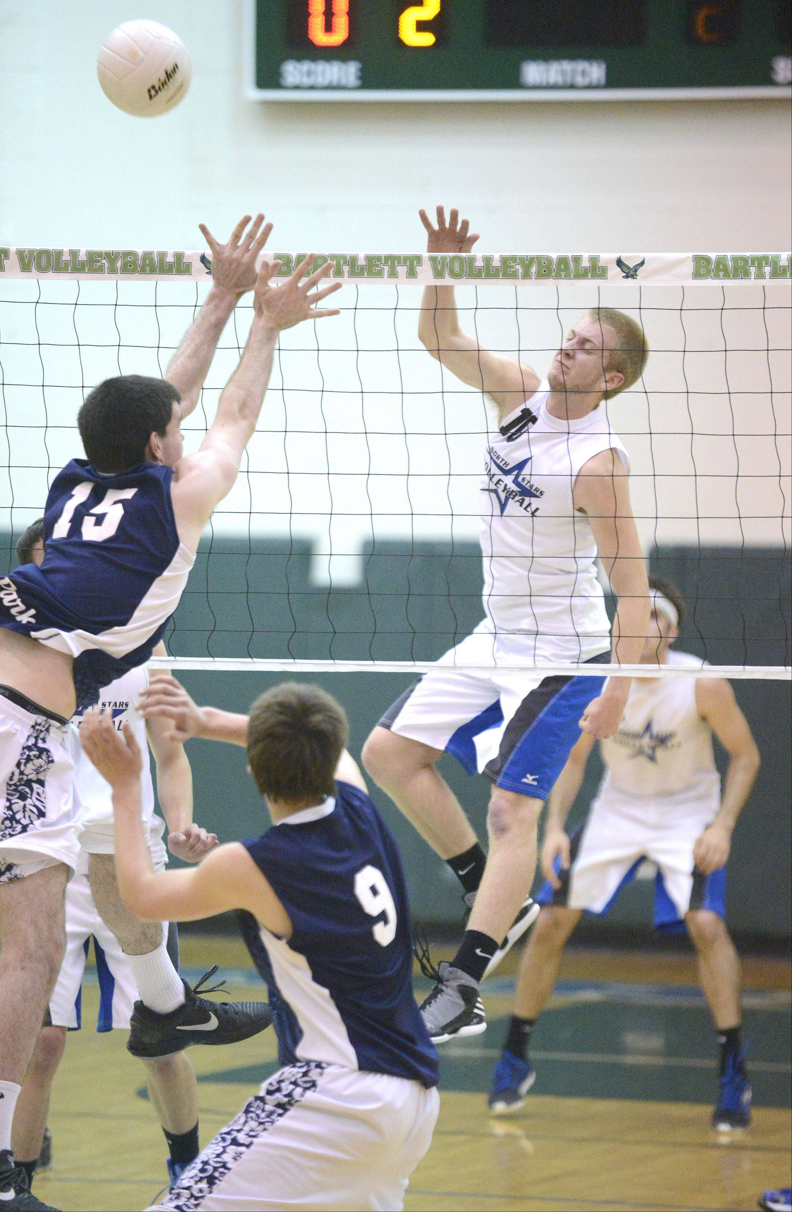Lake Park's Sean Moore and Quin Krisik attempt a block on a spike by St. Charles North's Kevin Beach in the first game of sectional championship play in Bartlett on Tuesday.