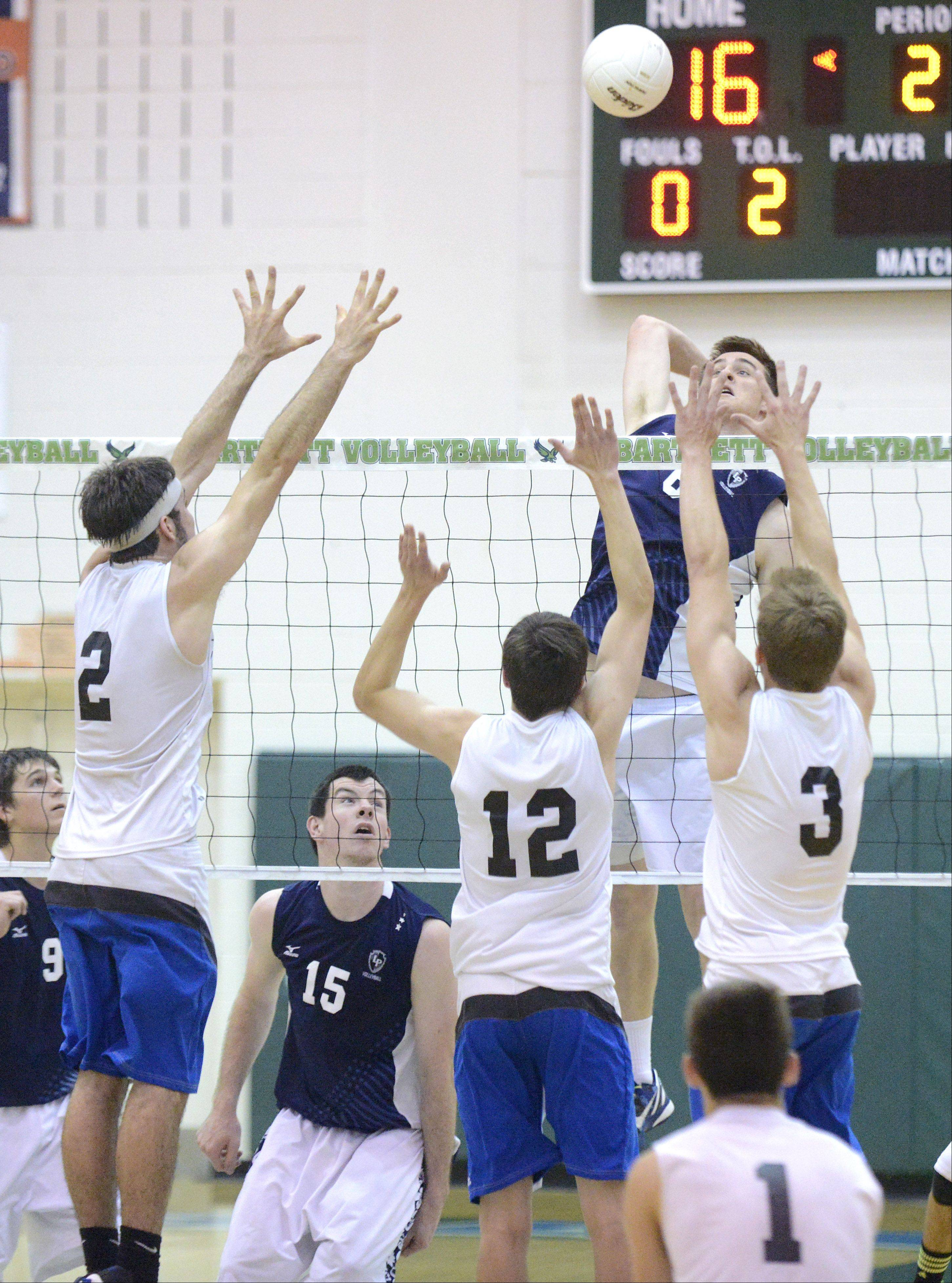 Lake Park's Dillon Hock spikes the ball into a block by St. Charles North's Jonathan Orech, Jake Hamilton and Pat Misiewicz in the second game of the sectional championship at Bartlett on Tuesday.