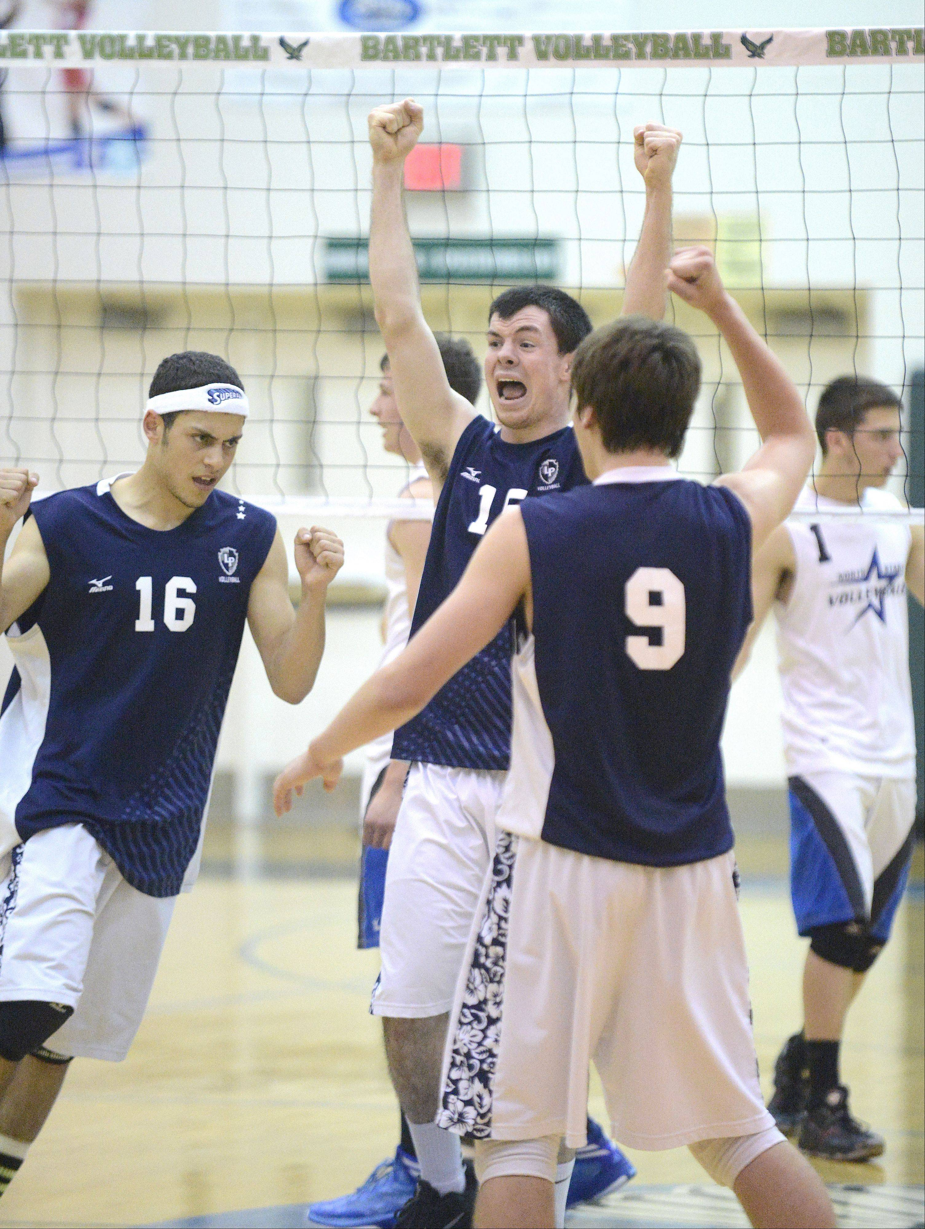 Lake Park's Sean Moore, center, celebrates a point over St. Charles North with teammates Dominick Terry (16) and Quin Krisik (9) in the first game of sectional championship play in Bartlett on Tuesday.