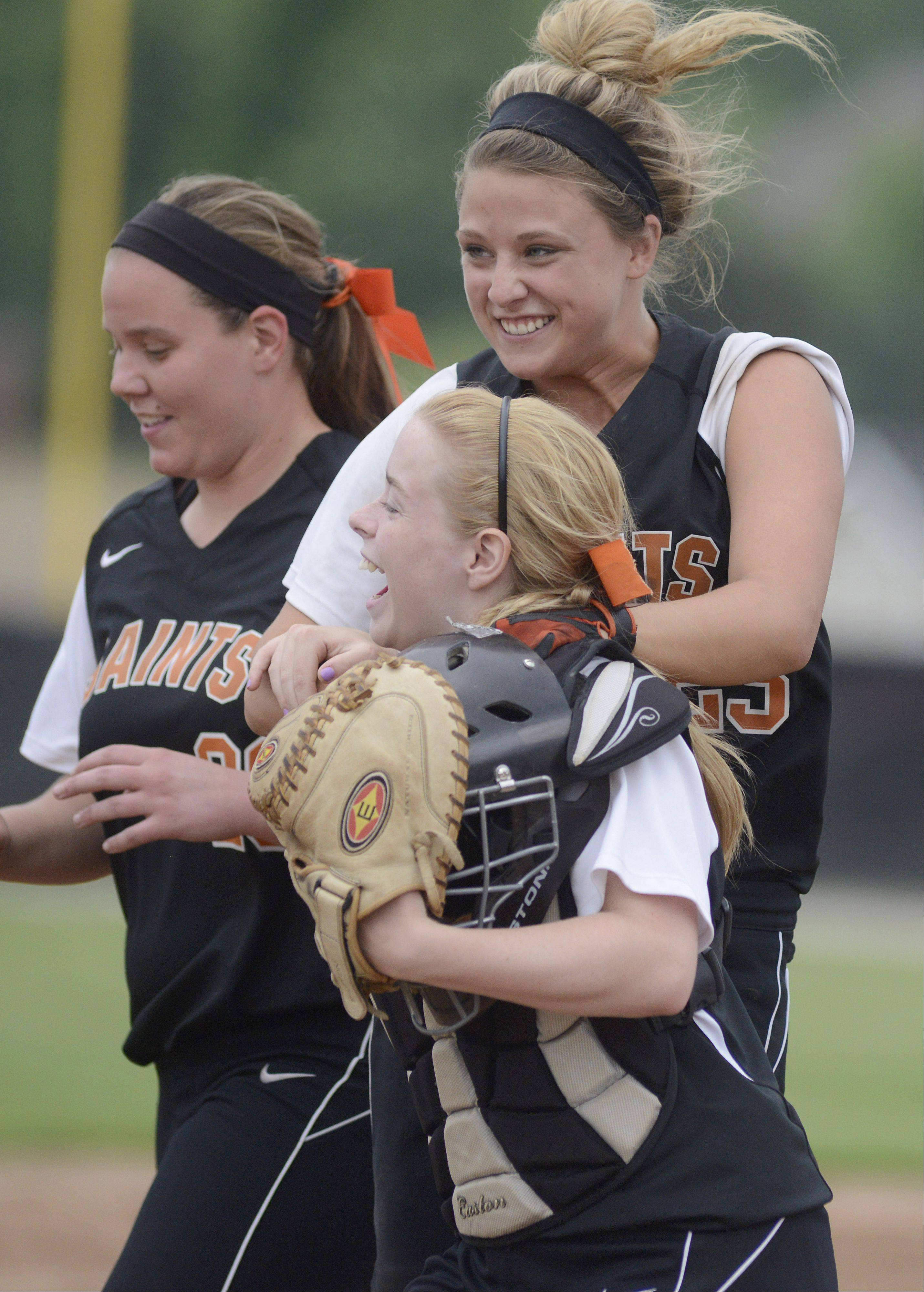 St. Charles East's Mackenzie Meadows jumps with her arms wrapped around teammate and catcher Shelby Holtz after winning the Class 4A sectional vs. Bartlett on Tuesday.