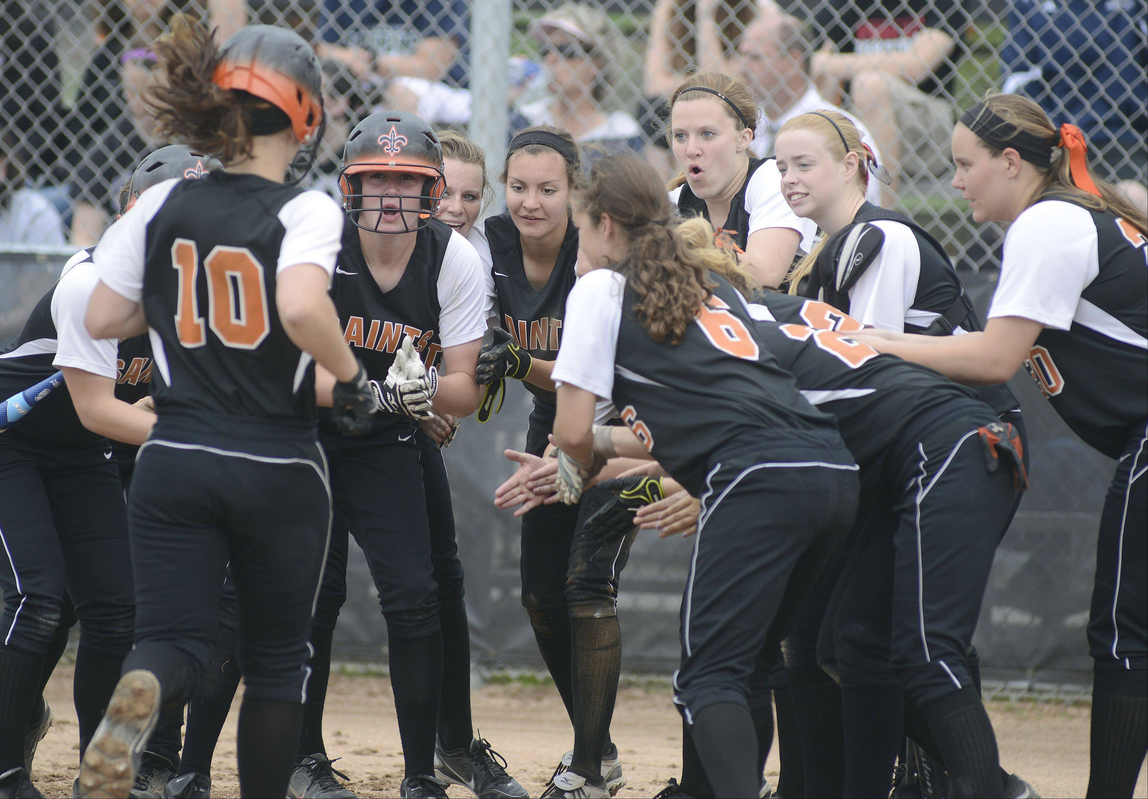 St. Charles East's Kate Peterburs is welcomed at home plate after hitting a home run in the first inning of the Class 4A sectional on Tuesday.