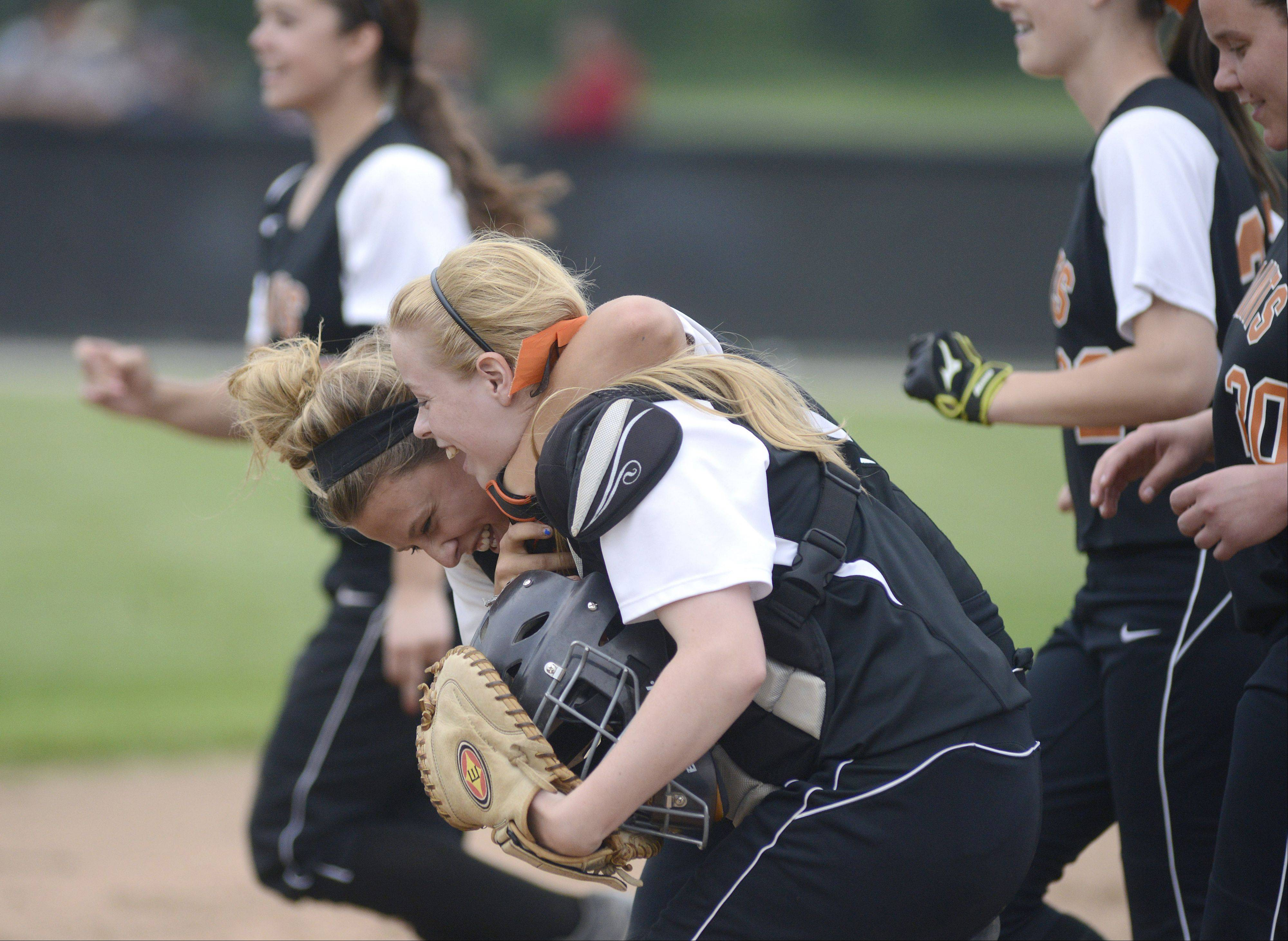 St. Charles East's Mackenzie Meadows wraps her arm around teammate and catcher Shelby Holtz after winning the Class 4A sectional vs. Bartlett on Tuesday.