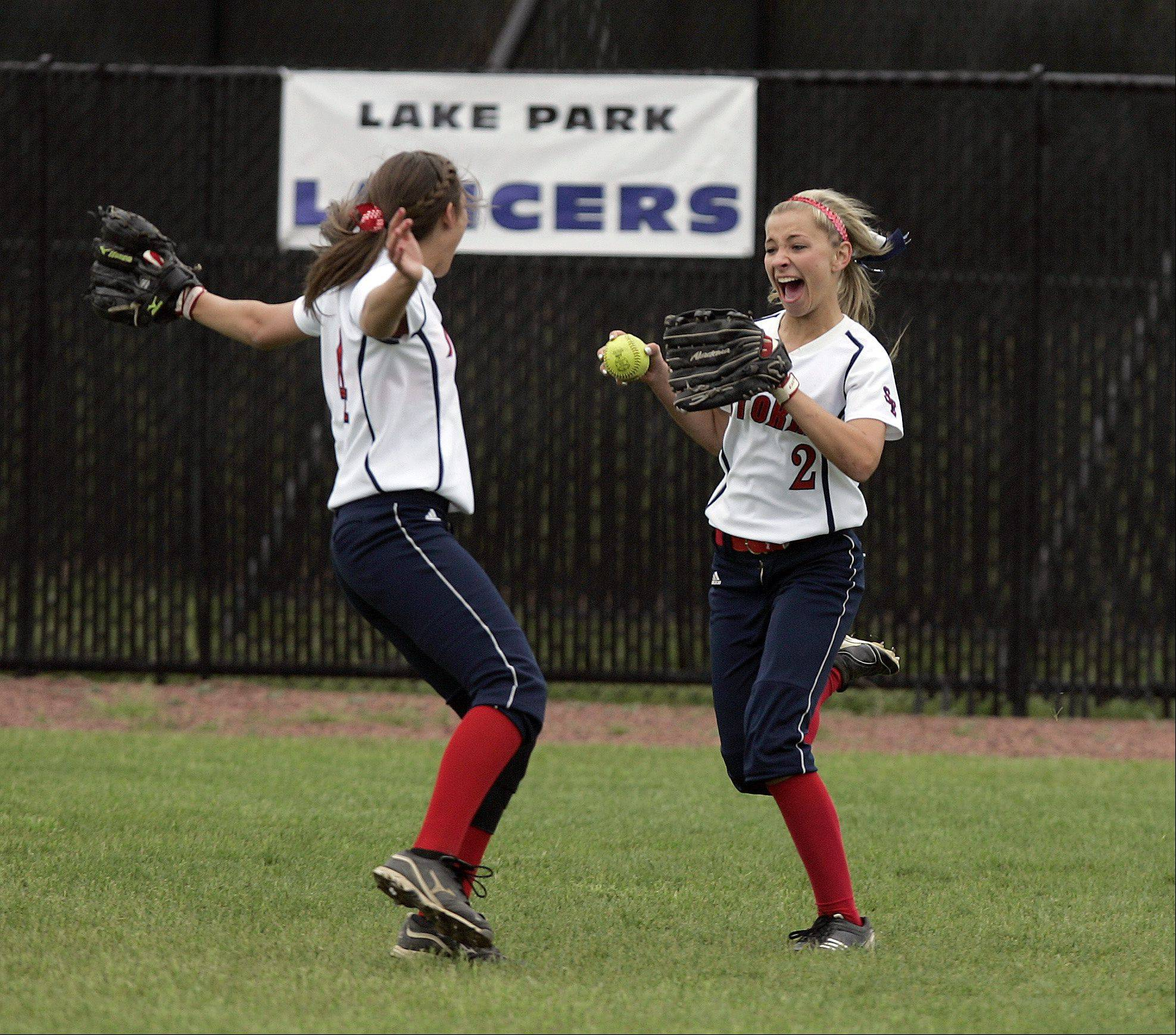 South Elgin's Mallory Mecklenburg, 2, is greeted by Brittany Koss, 4, after pulling in the last out of the Class 4A regional softball finals against St. Charles North Saturday.