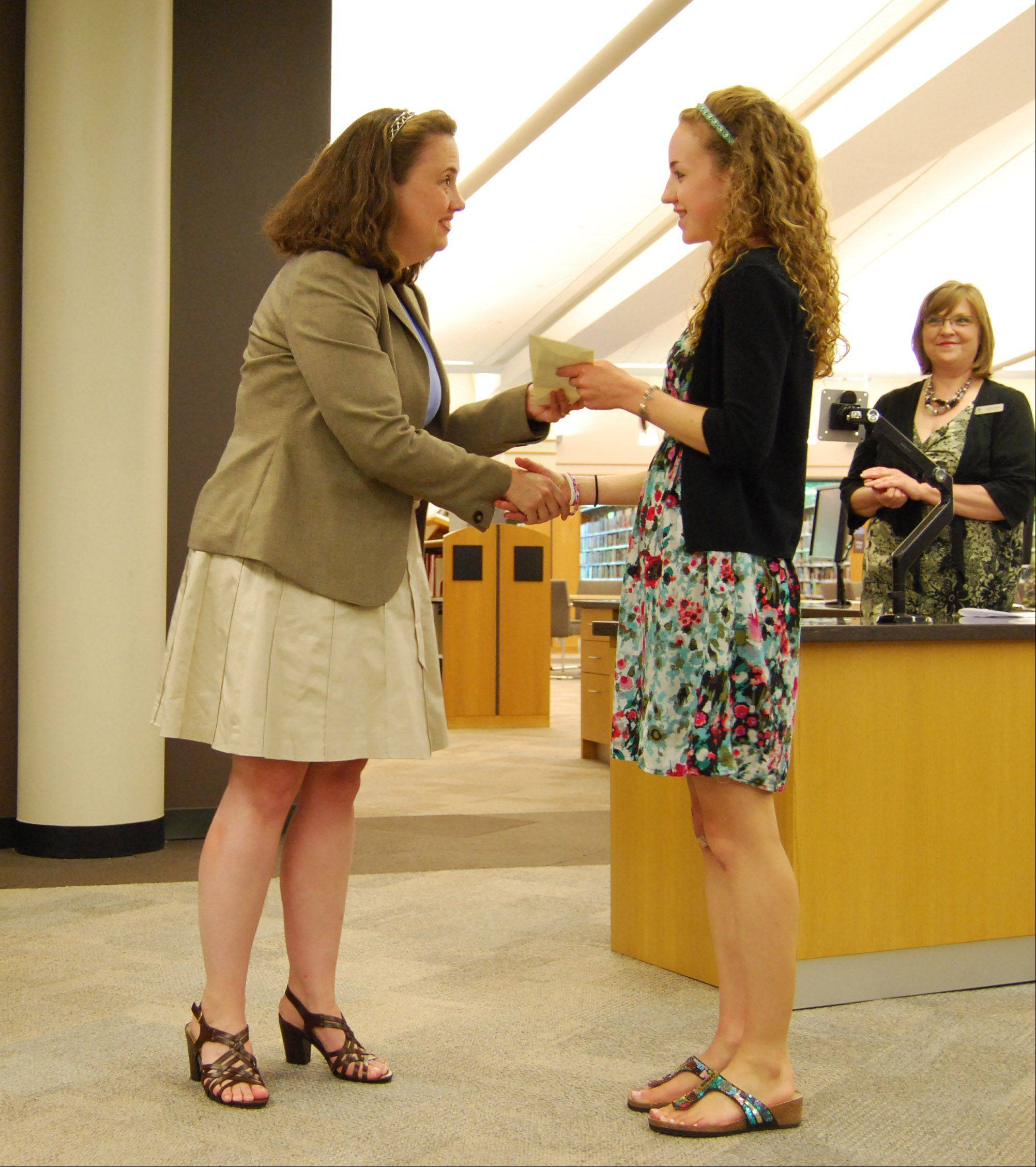Melissa Engel, a senior at Stevenson High School, receives the 2013 Allen E. Meyer Memorial Scholarship award from Angie Goodrich, president of the Friends of the Vernon Area Library while library director Cynthia Fuerst looks on.