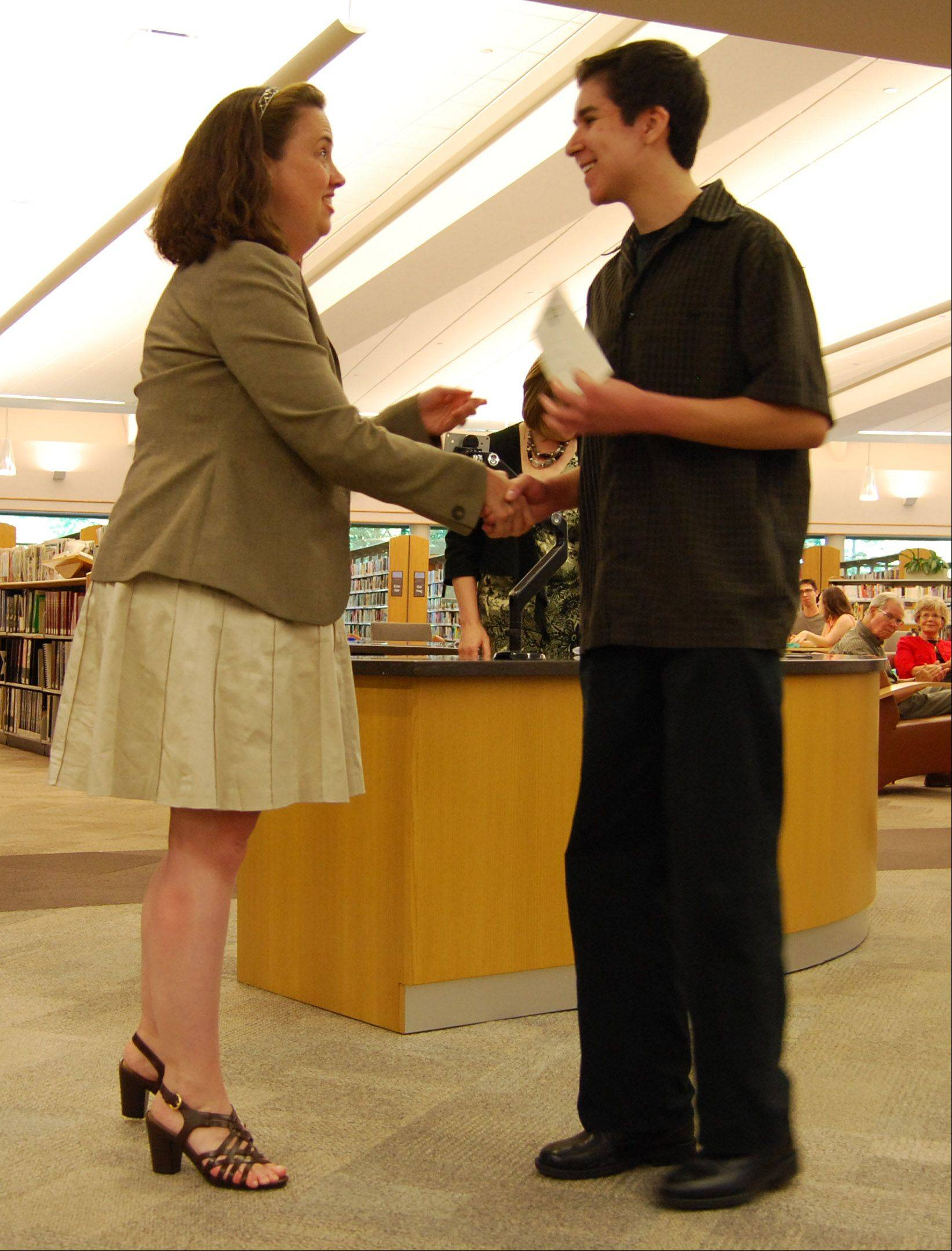 Angie Goodrich, president of the Friends of the Vernon Area Library, presents Stevenson High School senior Jeffrey Epstein with the first honorable mention award of the annual Allen E. Meyer Memorial Scholarship.
