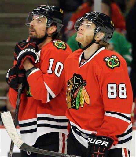 Chicago Blackhawks' Patrick Kane (88) and Patrick Sharp (10) check a score board during the first period of Game 5 of the NHL hockey Stanley Cup playoffs Western Conference semifinals against the Detroit Red Wings in Chicago, Saturday, May 25, 2013. (AP Photo/Nam Y. Huh)