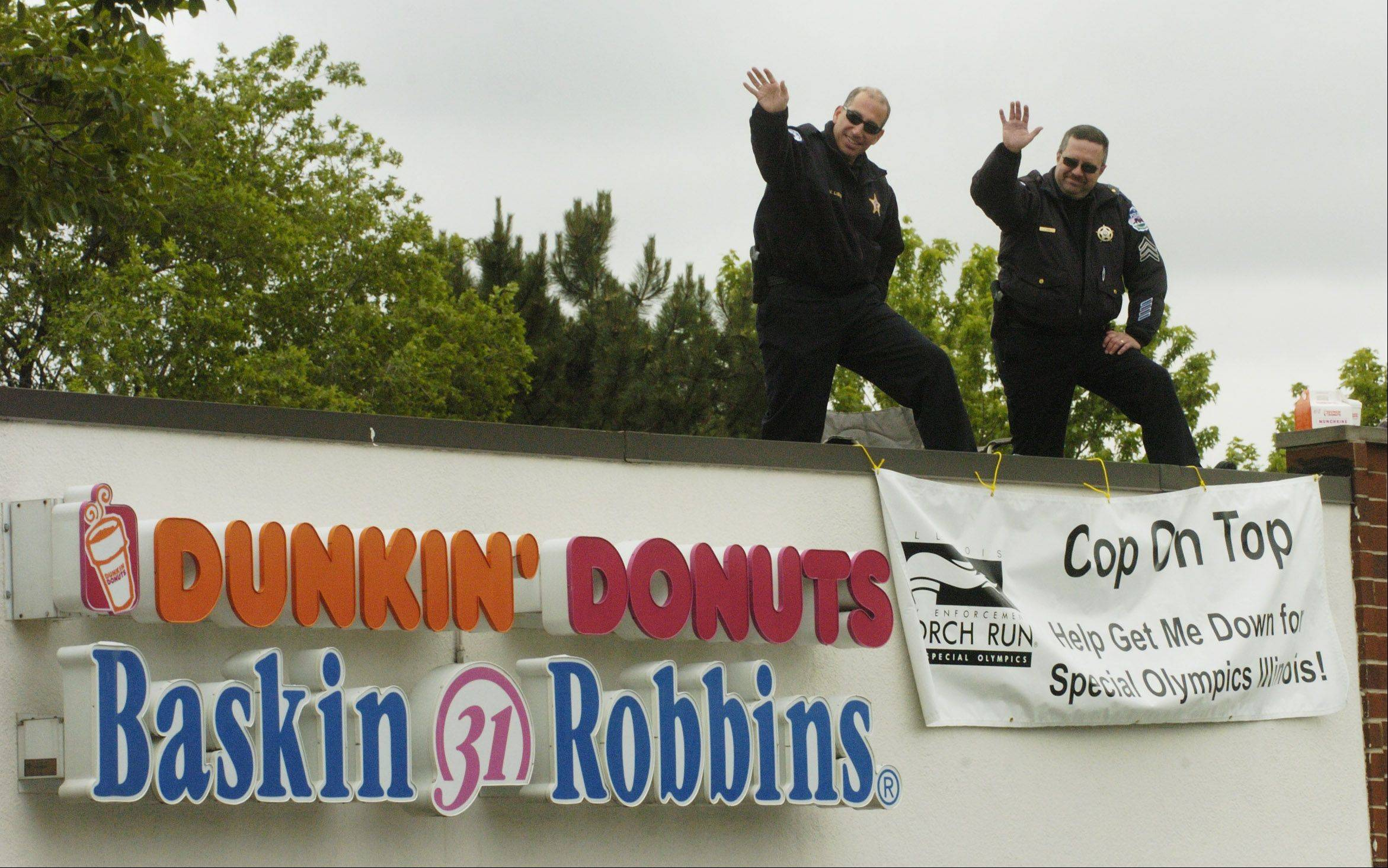 In 2012, Schaumburg police wave to patrons from the rooftop of the Dunkin' Donuts at Schaumburg and Plum Grove roads.