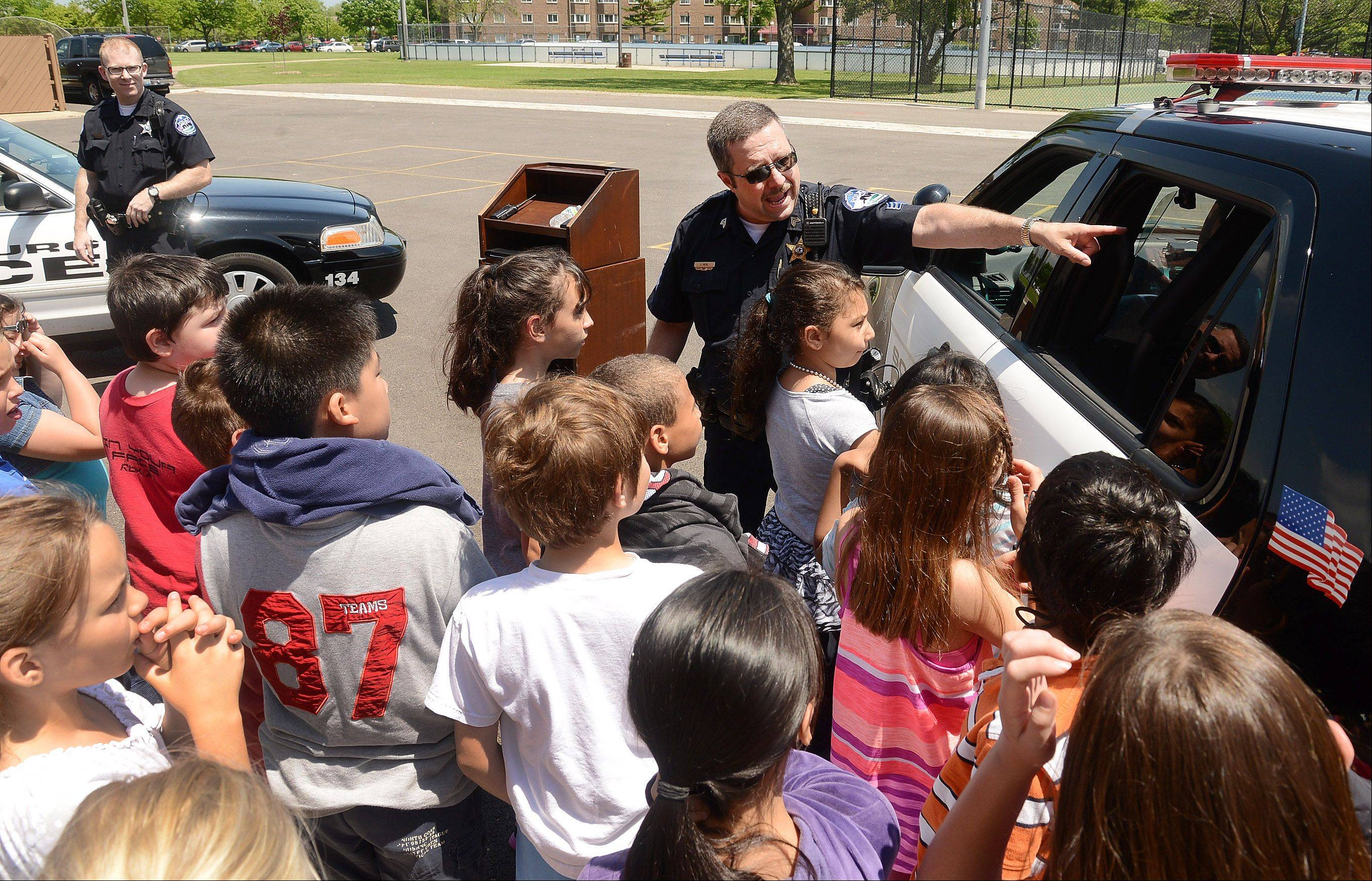Schaumburg Police Sgt. John Nebl explains to third and fourth graders at Dirksen Elementary School some of the latest technology in the new police SUV and squad car.