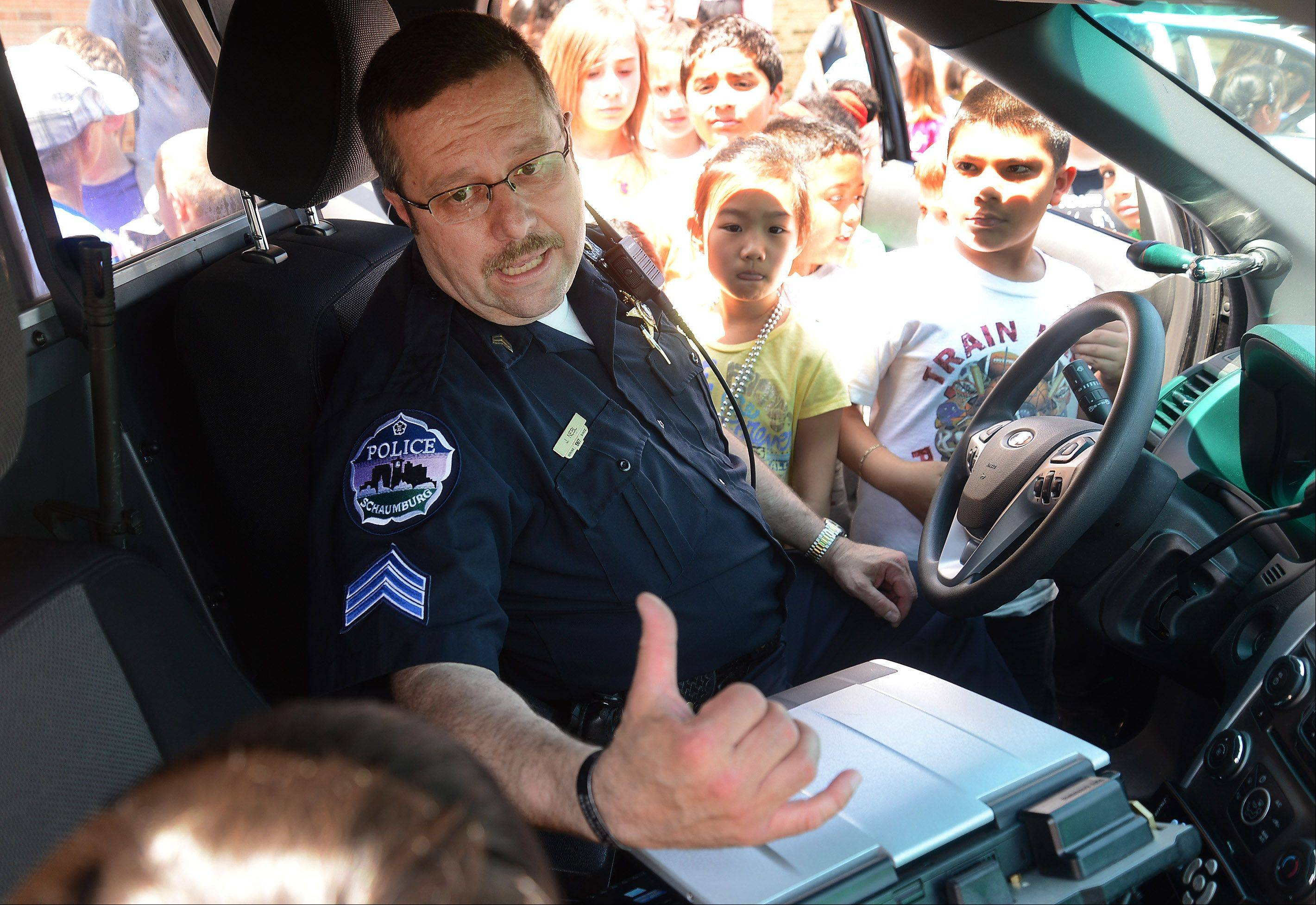 Schaumburg Sgt. John Nebl explains some of the latest technology inside the new police SUV to third and fourth graders at Dirksen Elementary School Wednesday.