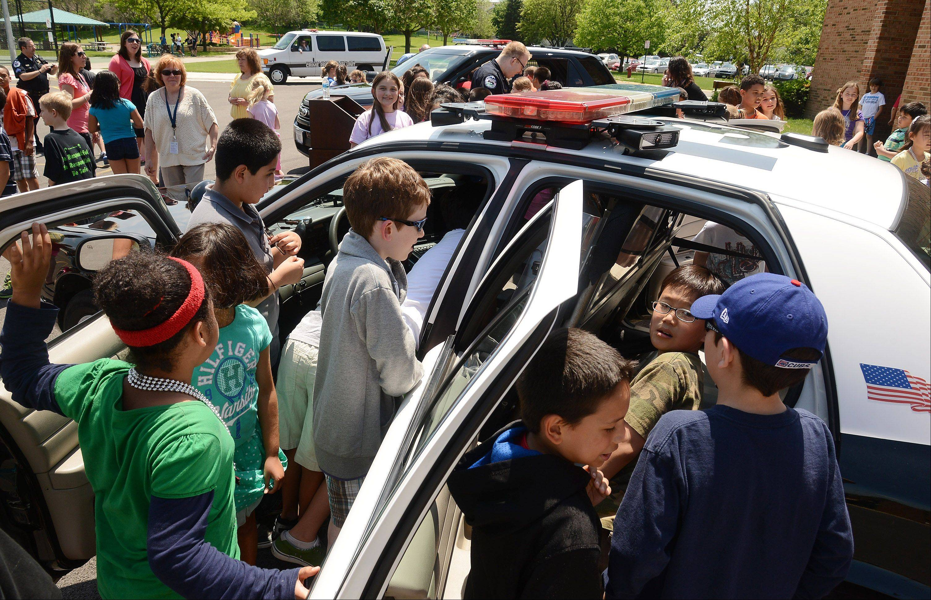 Schaumburg police unveil a new police SUV and squad car to third and fourth graders at Dirksen Elementary School Wednesday.