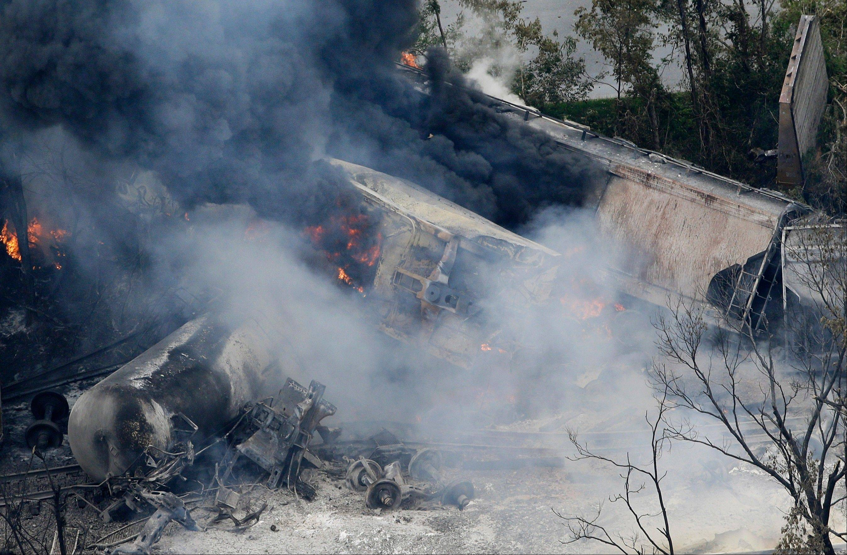 A fire burns at the site of a CSX freight train derailment, Tuesday, May 28, 2013, in Rosedale, Md., where fire officials say the train crashed into a trash truck, causing an explosion that rattled homes at least a half-mile away and collapsed nearby buildings, setting them on fire.