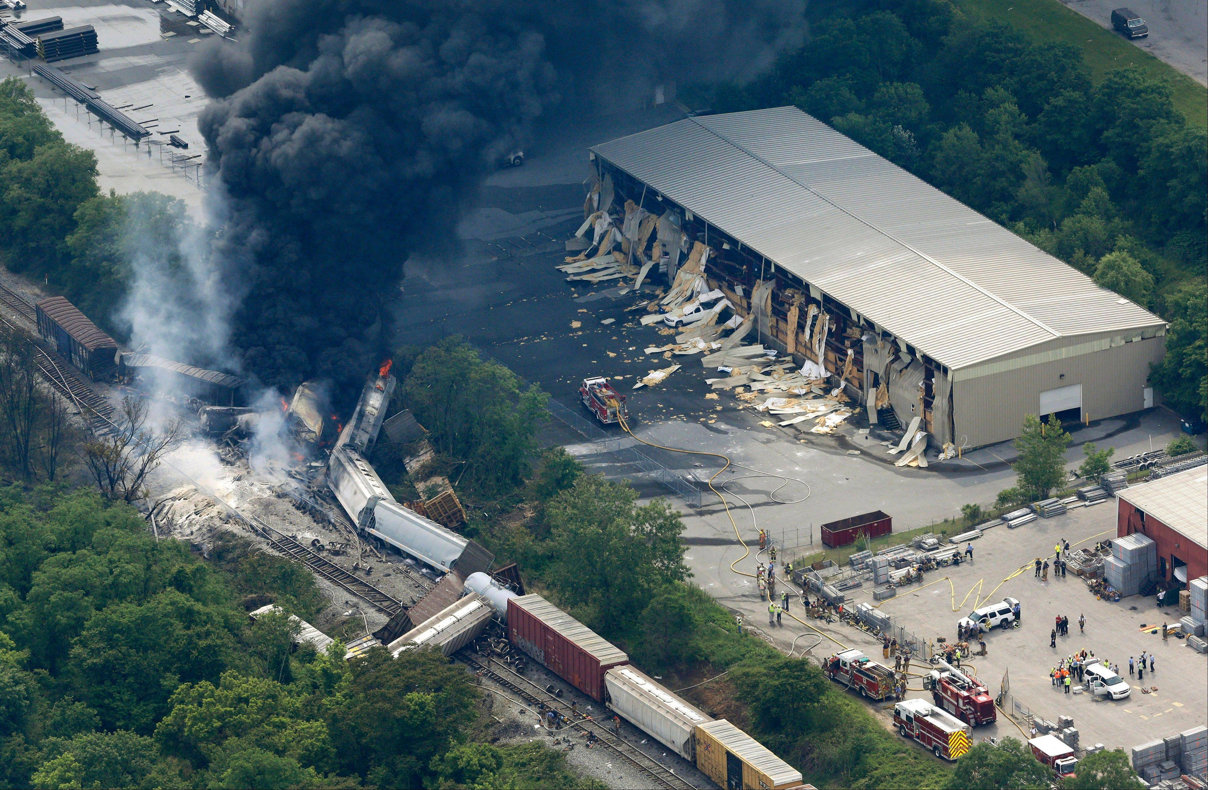 A fire burns at the site of a CSX freight train derailment, Tuesday, May 28, 2013, in Rosedale, Md., where fire officials say the train crashed into a trash truck, causing an explosion that rattled homes at least a half-mile away and collapsed nearby buildings.