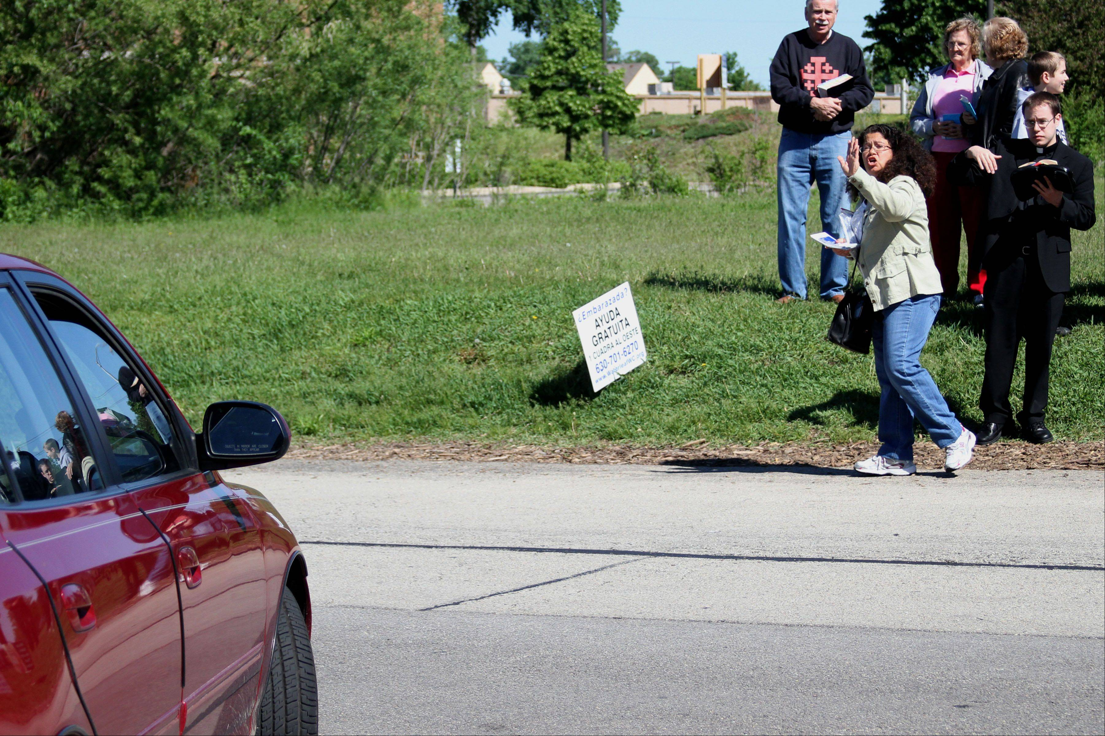 Aurora resident Marie Sulita flags down a passing car while handing out leaflets outside a Planned Parenthood clinic in Aurora.