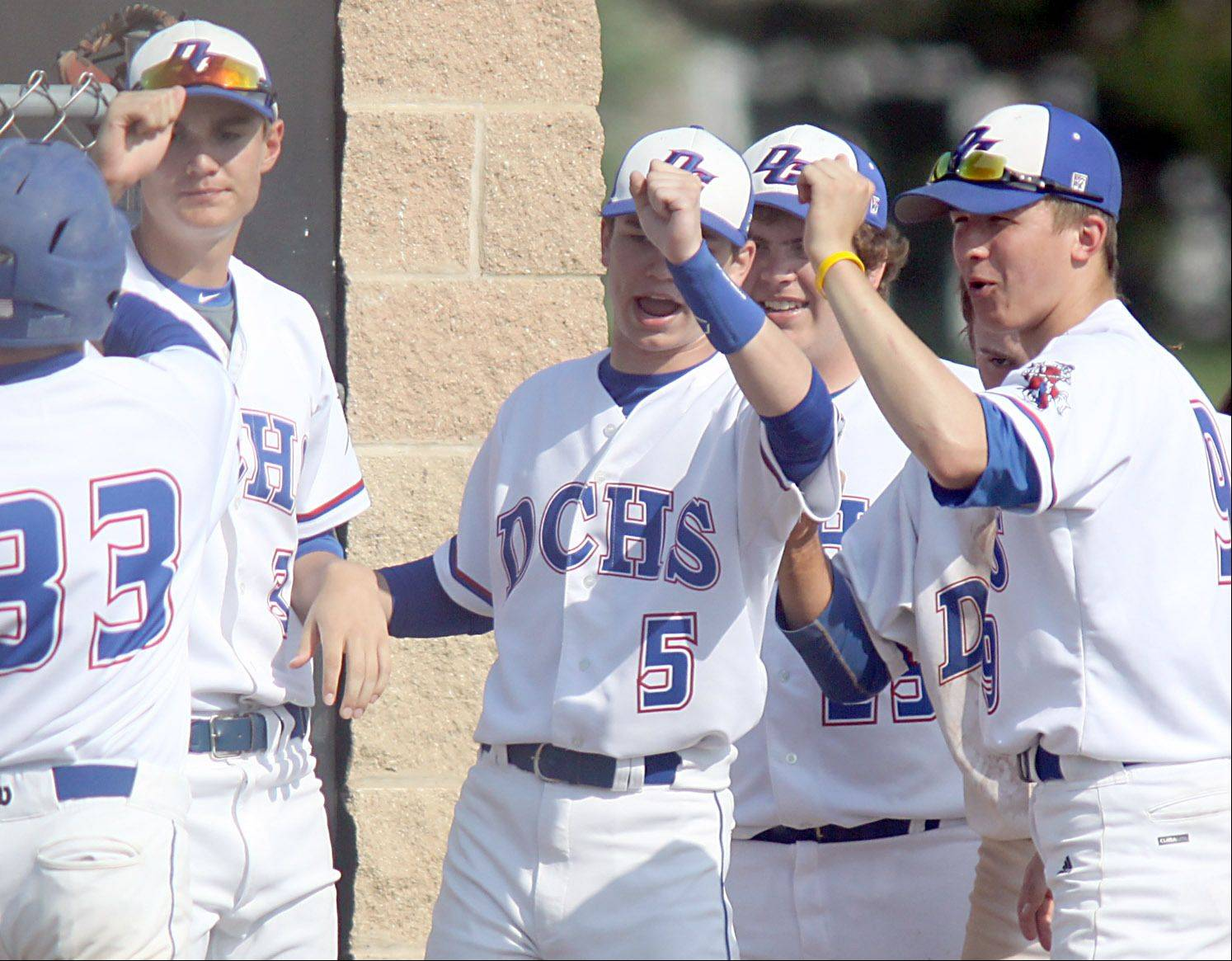 Dundee-Crown players greet Chase Bloch, far left, after Boch scored in the first inning during a sectional semifinal game at Huntley against Prairie Ridge on Wednesday night. The Chargers won 15-4.