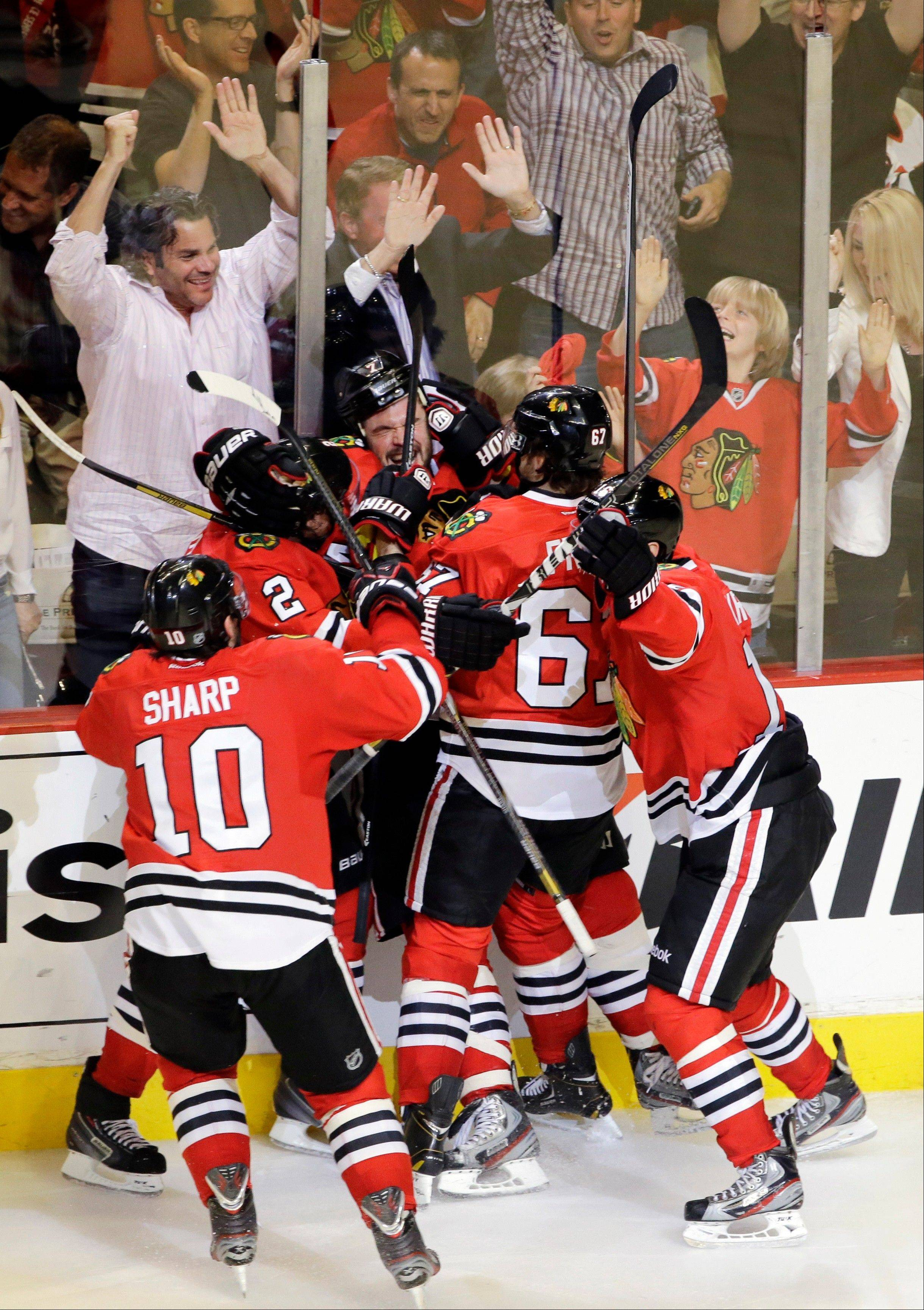 Chicago Blackhawks' Brent Seabrook, pinned to the wall, celebrates with his teammates after scoring in overtime in Game 7 of the NHL hockey Stanley Cup Western Conference semifinals against the Detroit Red Wings, Wednesday, May 29, 2013, in Chicago. The Blackhawks won 2-1.