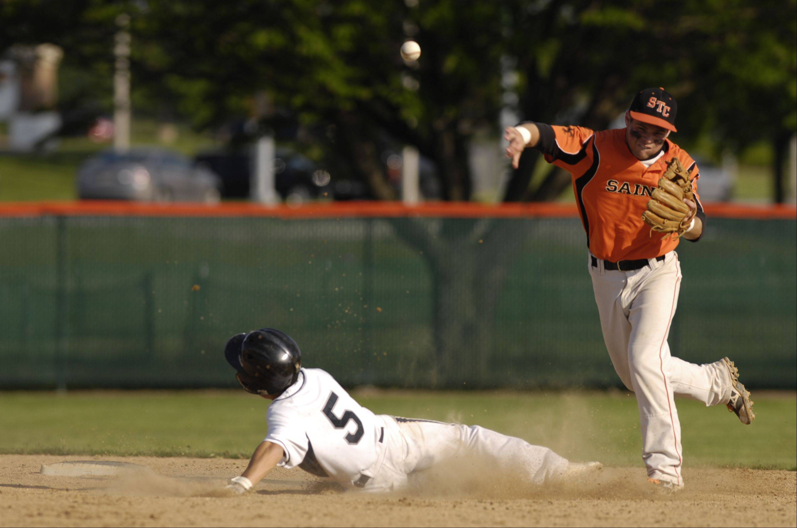 Nicholas Erickson of St. Charles East makes the out on Sam Pellegrino of Lake Park during the Saints 6-0 victory during the baseball sectional semifinals game, Monday in St. Charles.