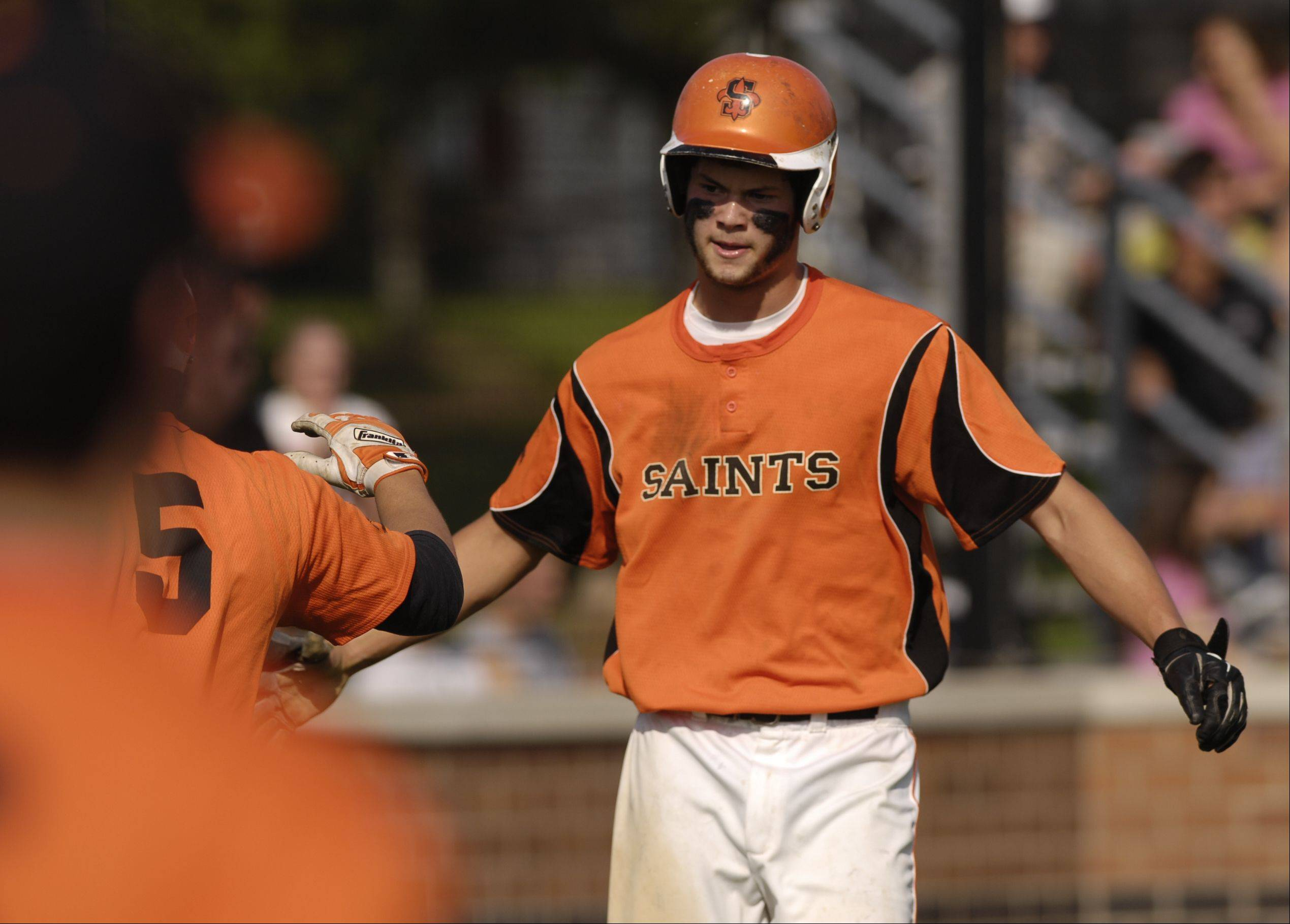 Brannon Barry of St. Charles East scores his teams 6th and finial run during the Saints 6-0 win over Lake Park during the baseball sectional semifinals, Monday in St. Charles.