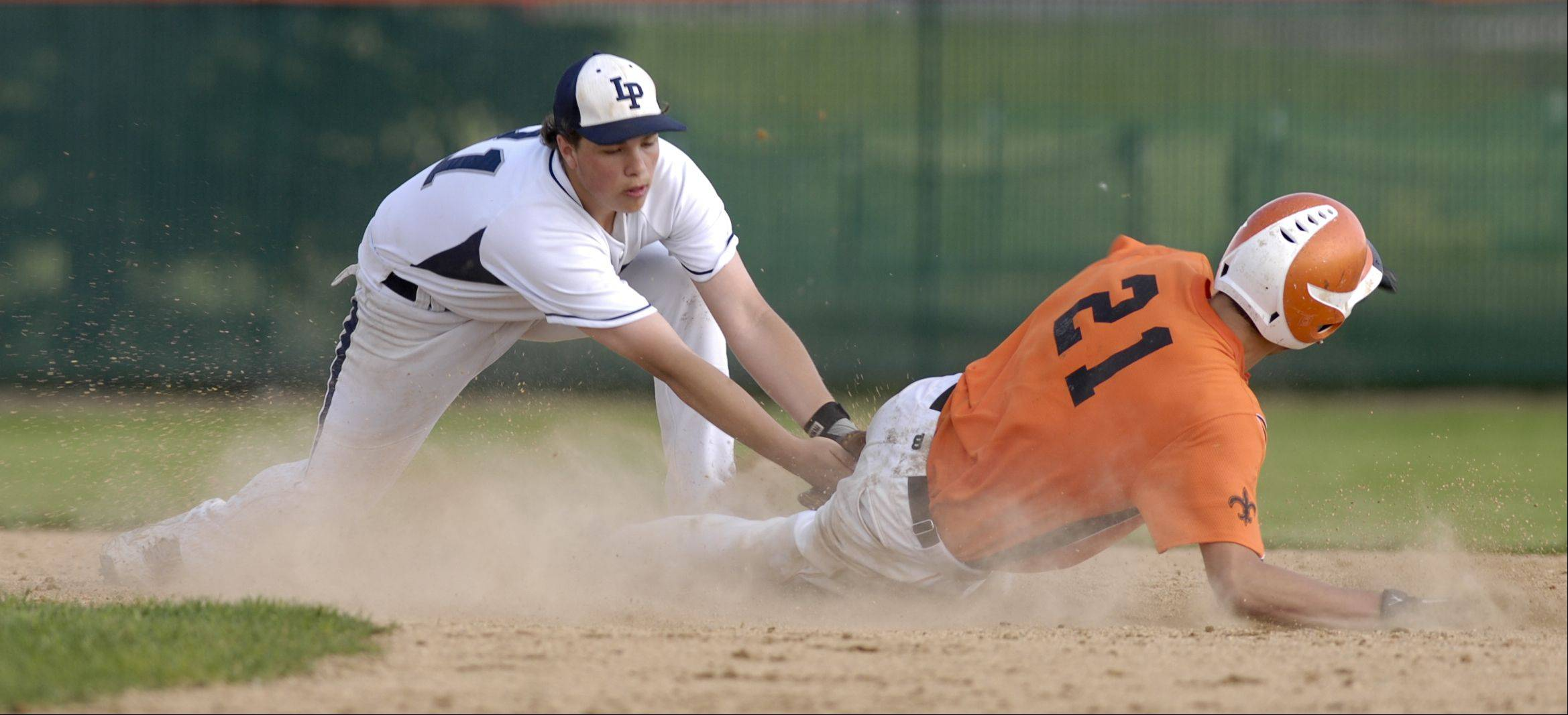 Ethan Schulz of Lake Park makes the out on Brannon Barry of St. Charles East baseball during at sectional semifinals, Monday in St. Charles.