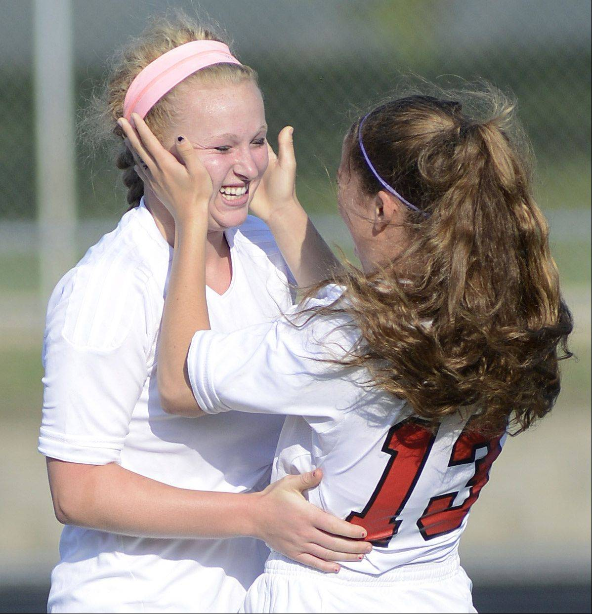 Barrington's Kelsey Muniz congratulates Molly Pfeiffer (10) after Pfeiffer scores a goal minutes into the first half of the Class 3A supersectional in Barrington on Wednesday.