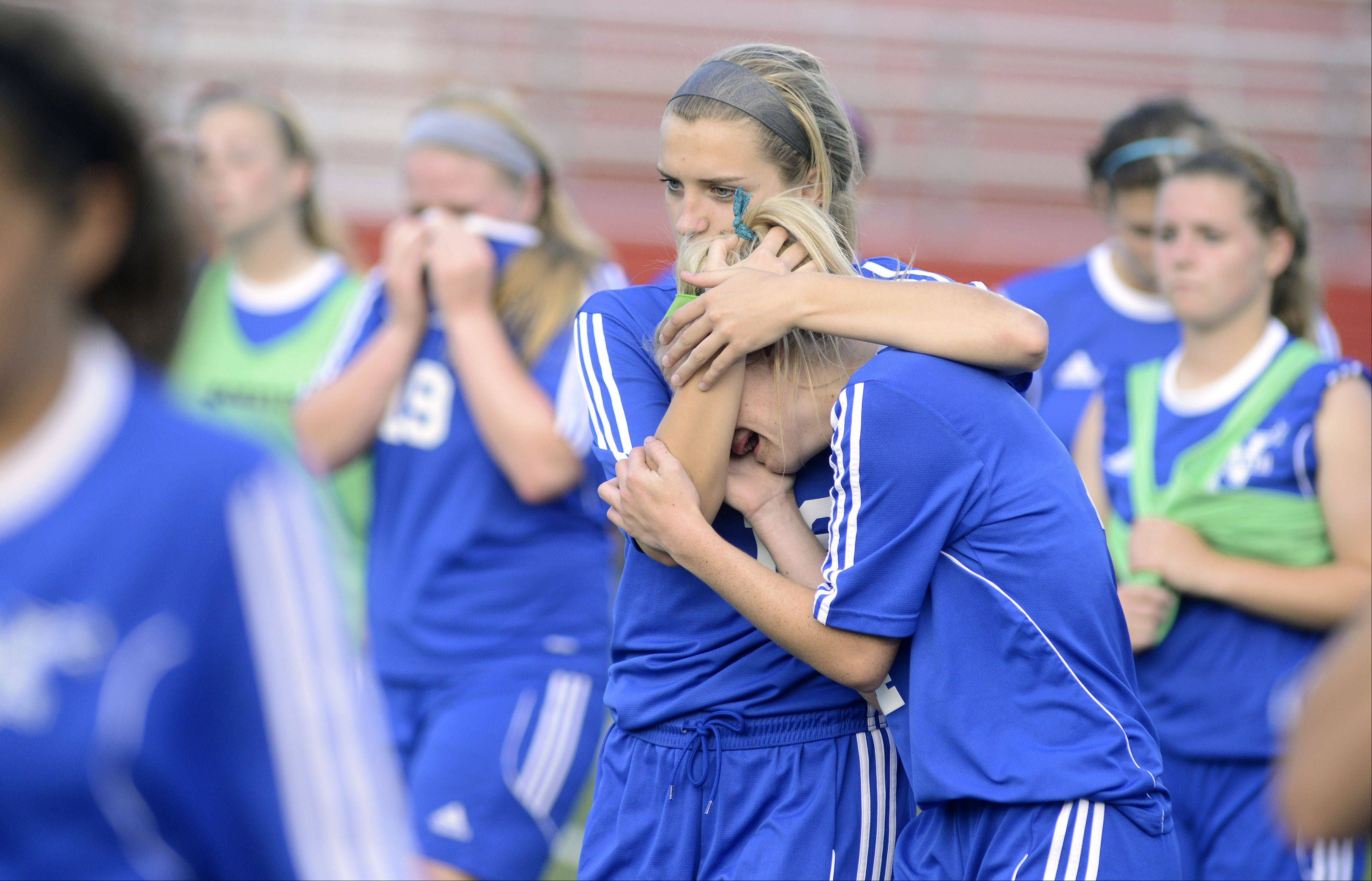 St. Charles North's Darcy Stoecklin comforts teammate Jenny Barr after the North Stars' Class 3A supersectional loss to Barrington on Wednesday.