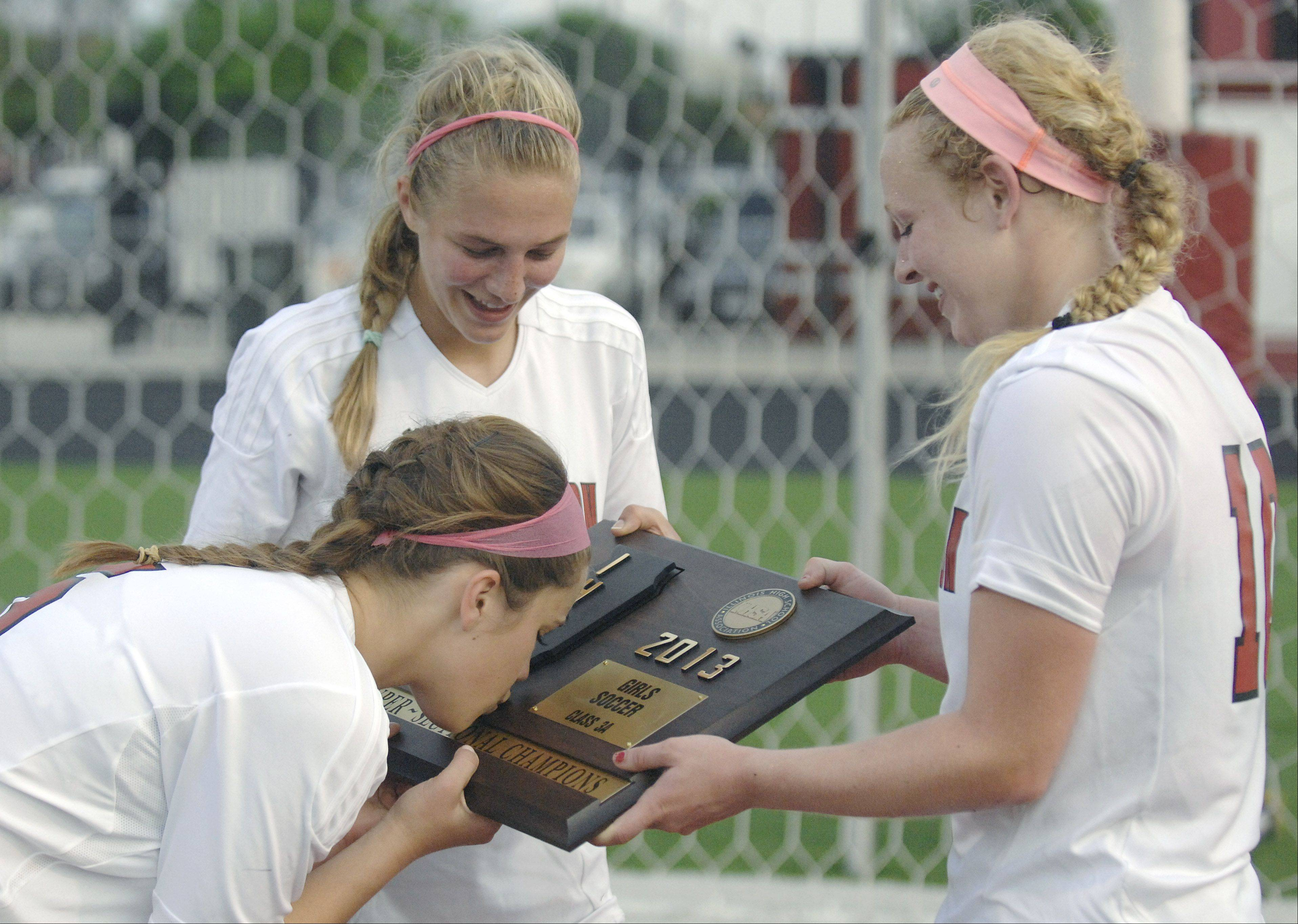Barrington's Jennifer Flannery kisses the trophy plaque while teammates Emily Morin, center, and Molly Pfeiffer, all seniors, giggle after their Class 3A supersectional win over St. Charles North in Barrington on Wednesday.