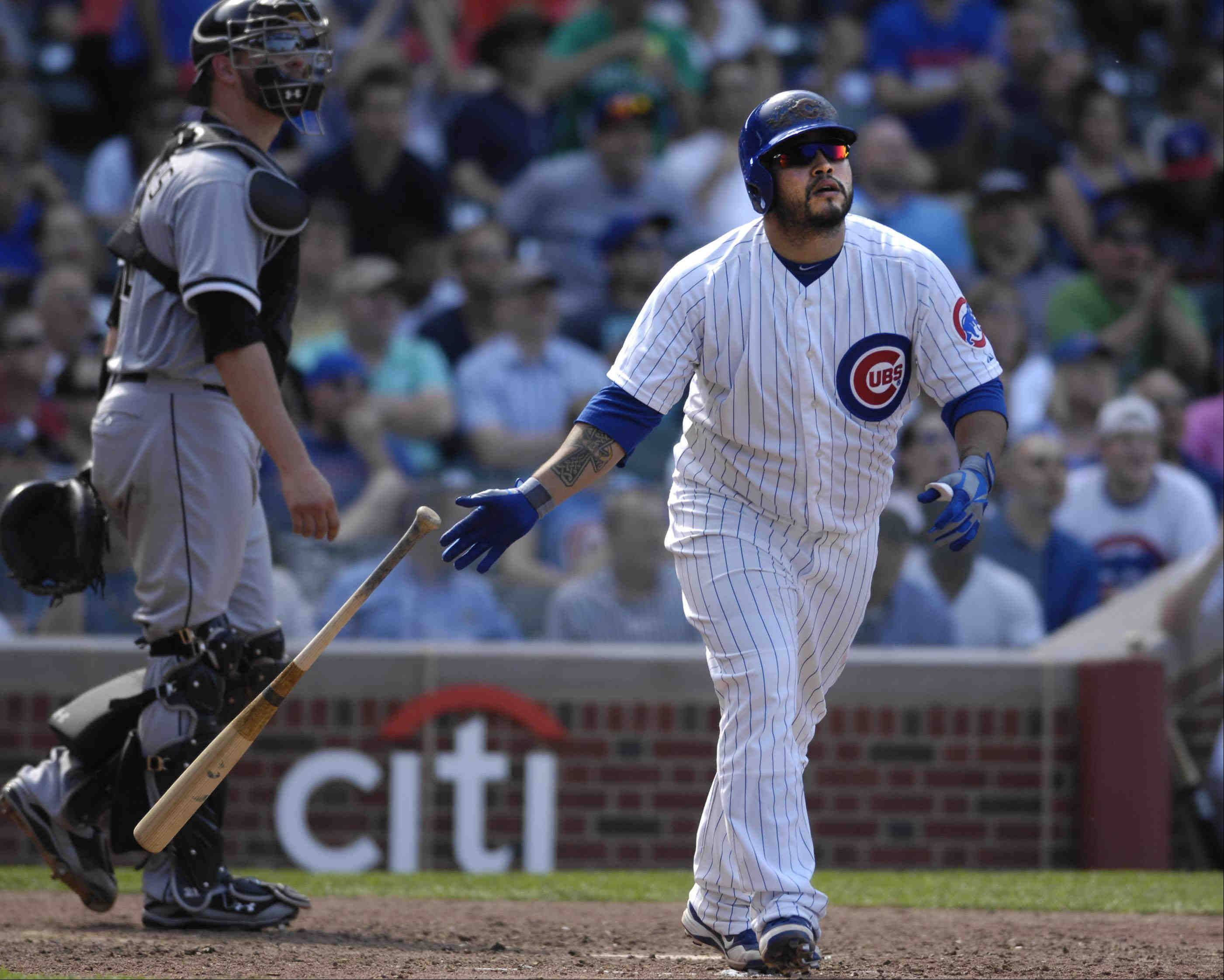 Chicago Cubs catcher Dioner Navarro tosses hit bat aside after hitting his third home run of the day.