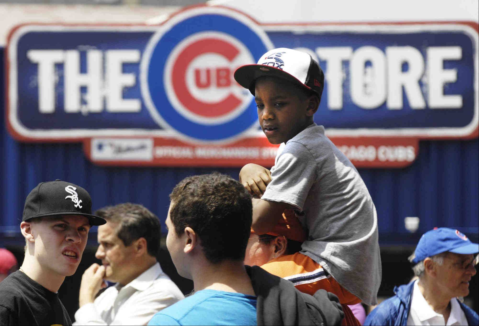 A young White Sox fan sits atop shoulders under the Wrigley field marquee.