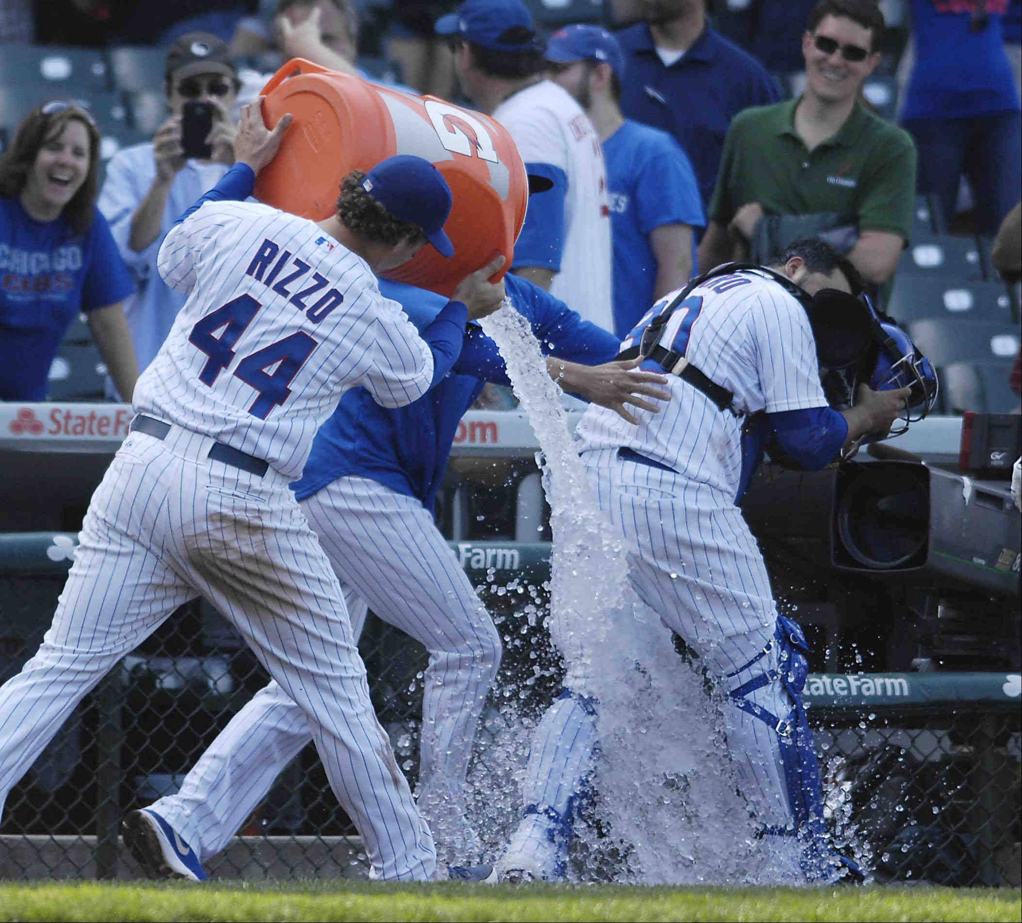 Chicago Cubs first baseman Anthony Rizzo dumps ice water on catcher Dioner Navarro after Navarro's three-home run game.