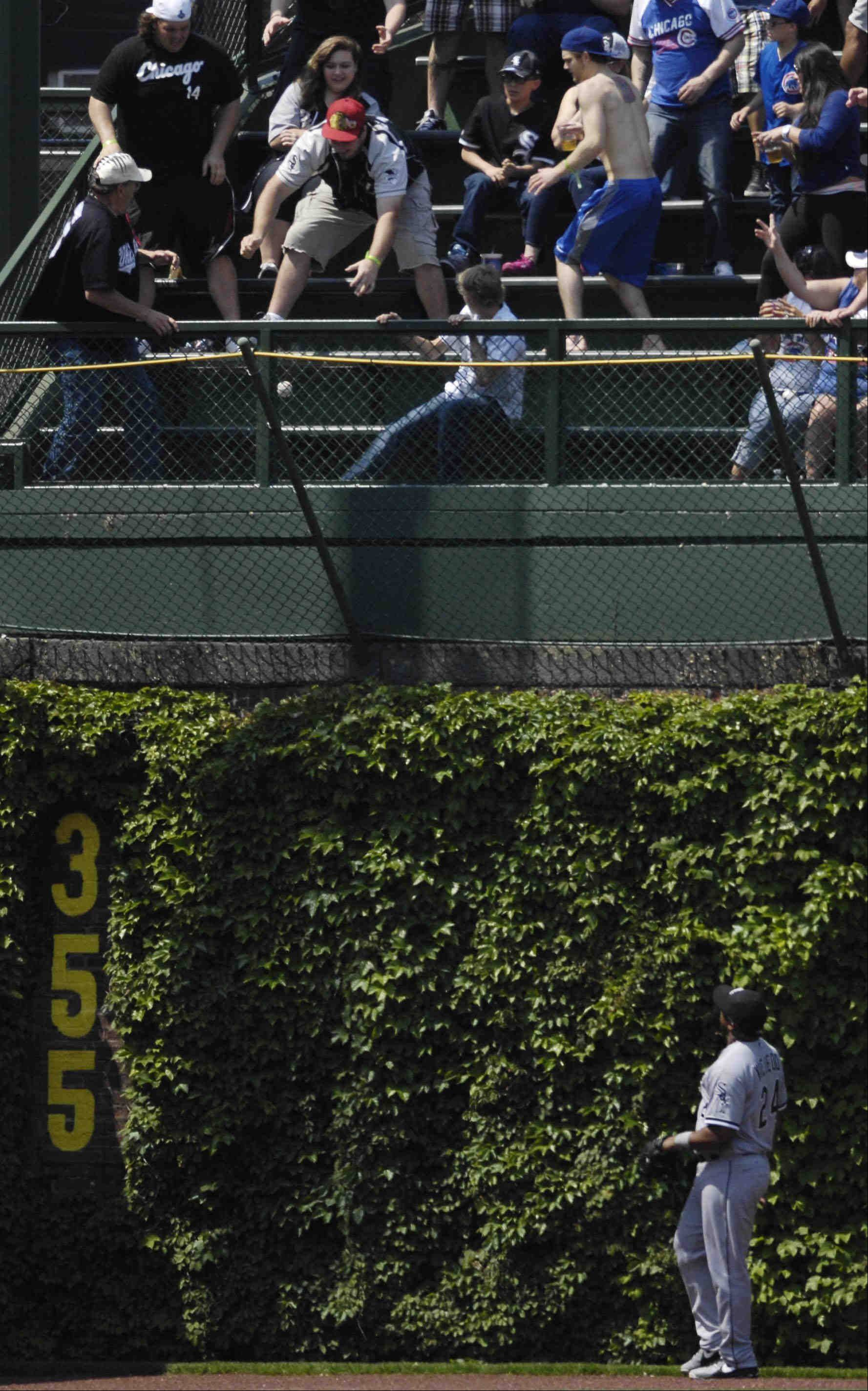 Left field bleacher fans scramble for Chicago Cubs catcher Dioner Navarro's second home run of the day.