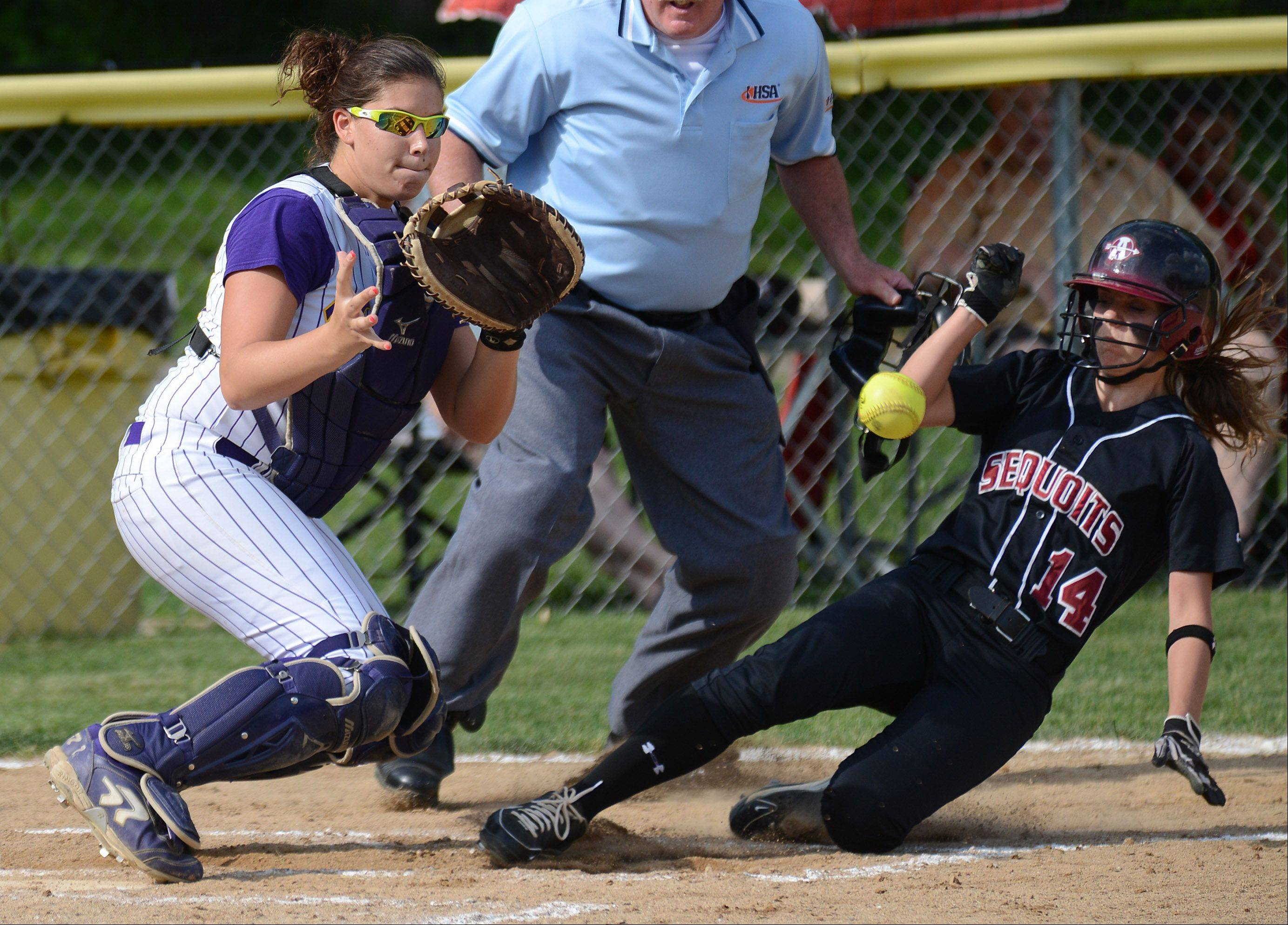 Antioch's Jessica Pedersen slides safely into home as Wauconda catcher Alex Kinnamon eyes the ball during Wednesday's Class 3A sectional semifinal in Grayslake.