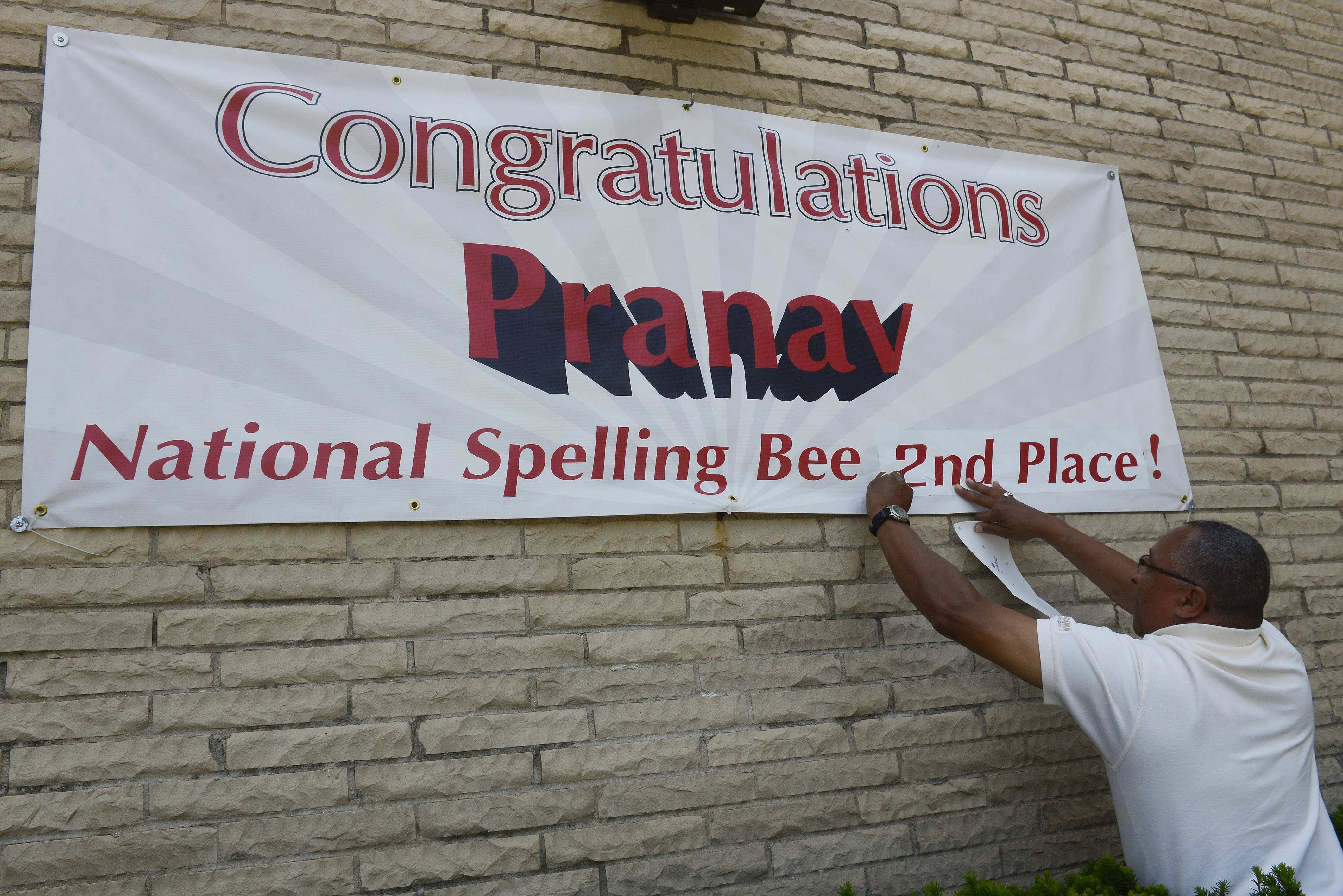 Vern Jones of Signaram in Barrington updates a banner Friday morning outside Barrington MIddle School Station Campus reflecting their pride in Pranav Sivakumar in the national spelling bee.