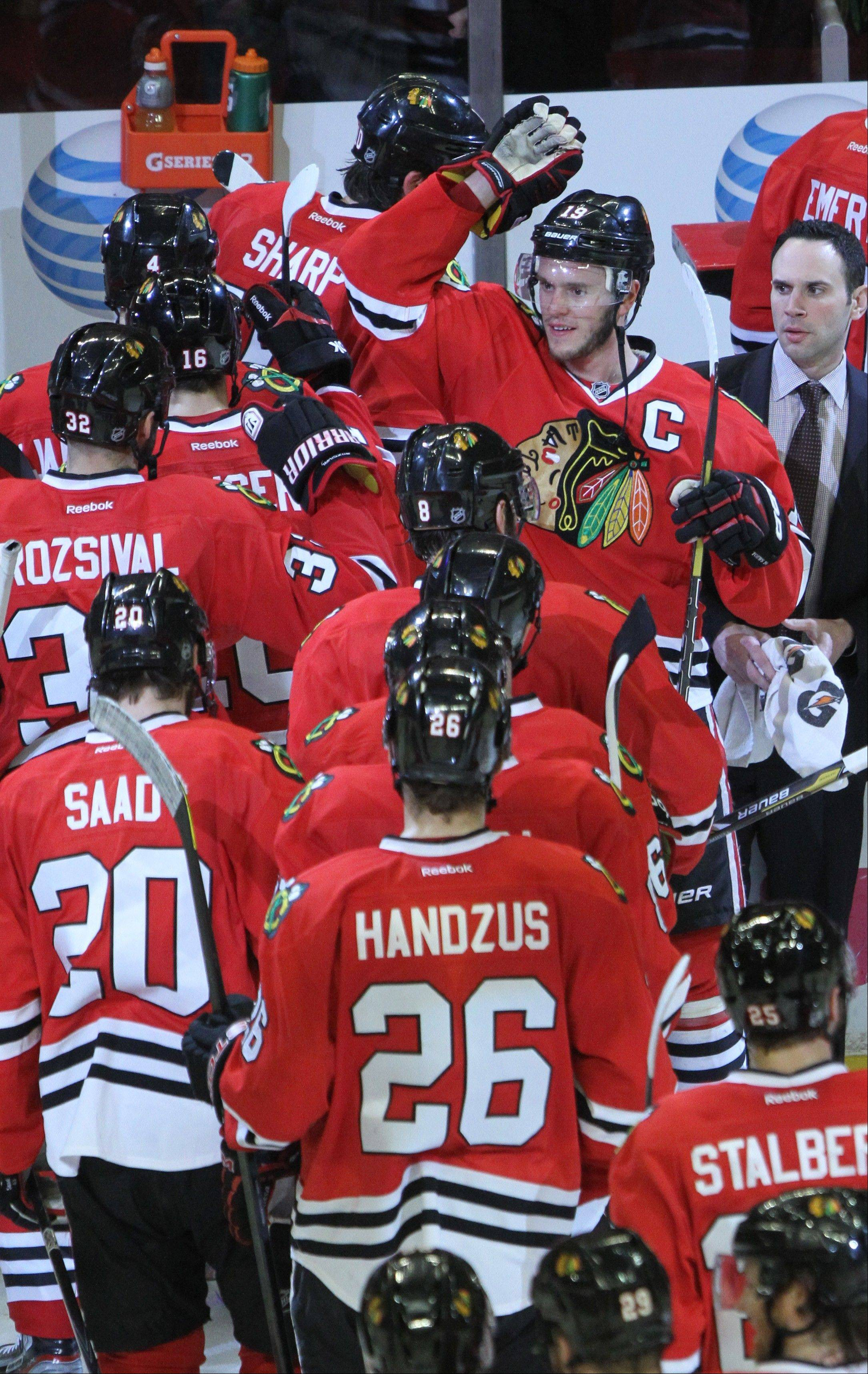 Blackhawks captain Jonathan Toews, top right, high-fives his teammates after their overtime win in Game 7 on Wednesday at the United Center.