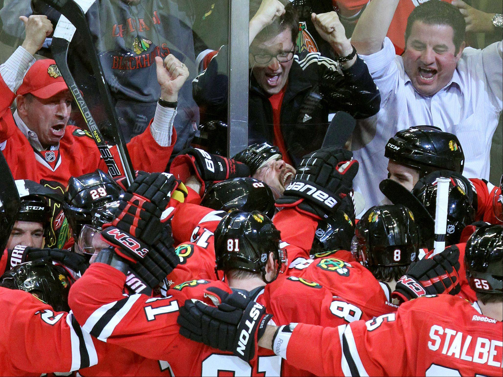 The Blackhawks mob Brent Seabrook after his overtime game-winning goal.