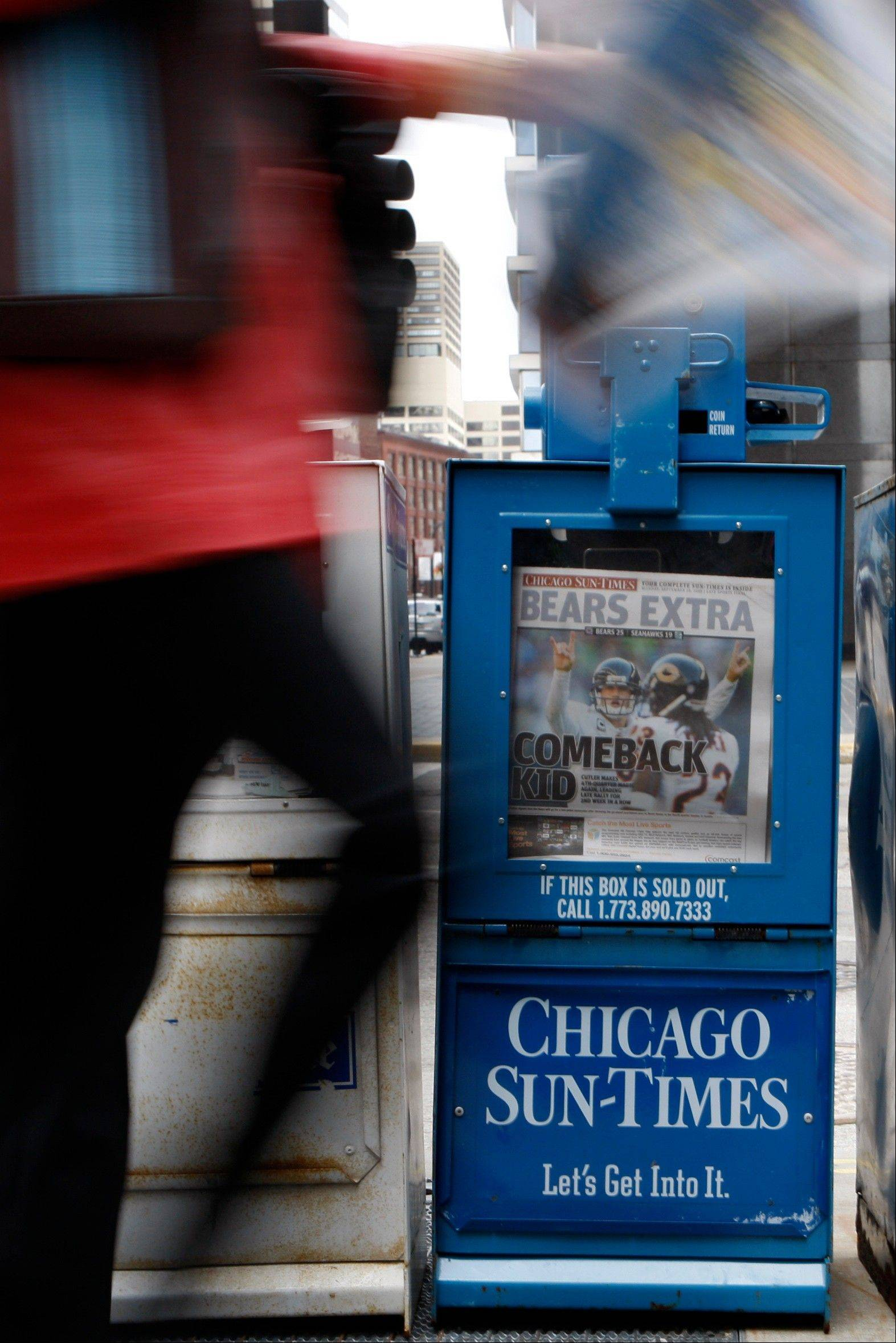 Pedestrians pass a Chicago Sun-Times newspaper box in Chicago. The company laid off nearly its entire photography staff on Thursday.