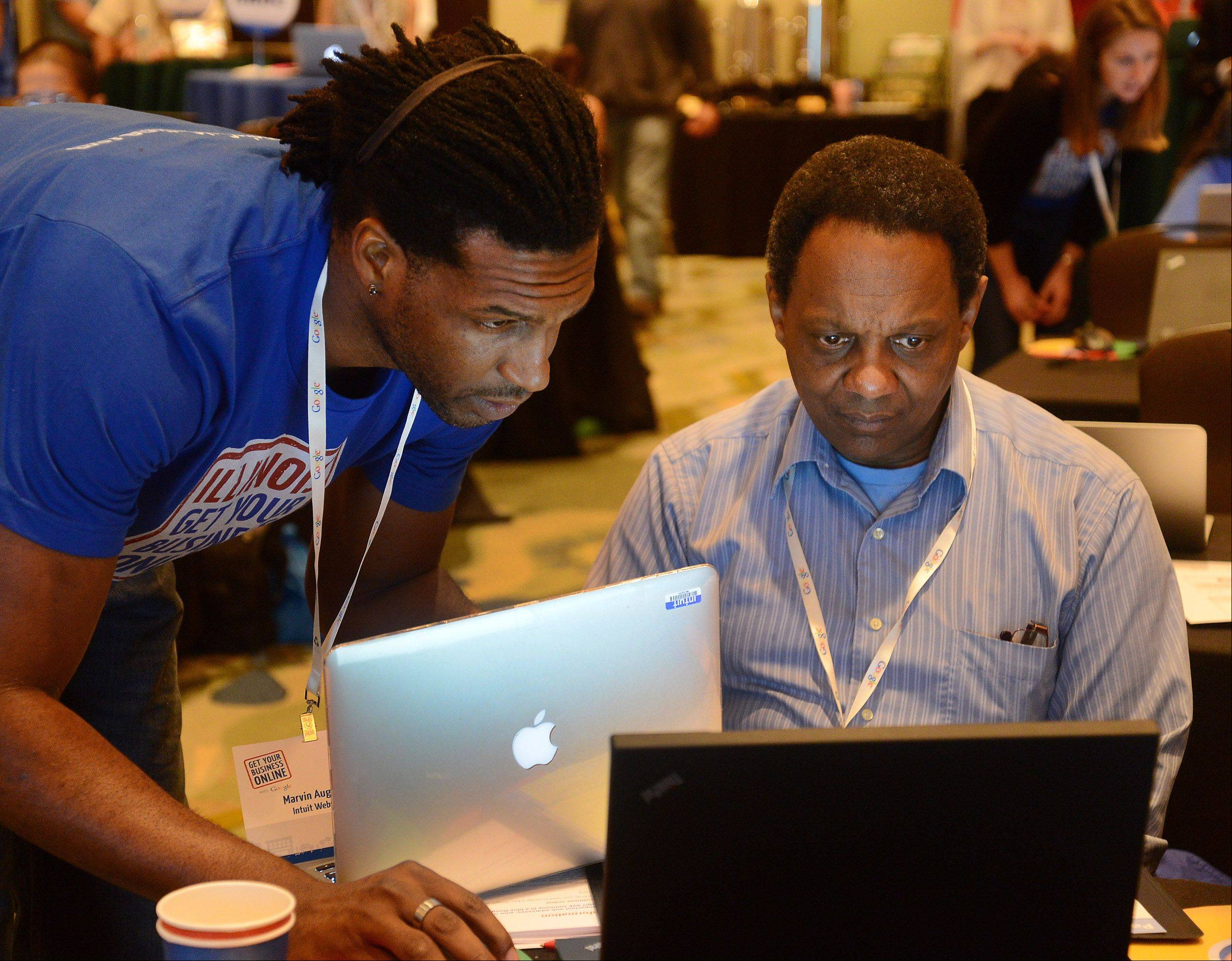 Marvin Augustin of Intuit web design, left, helps James Harvey of James Harvey Photography in Elgin, at Google's event Wednesday to help local businesses get a functional website up and running for free.