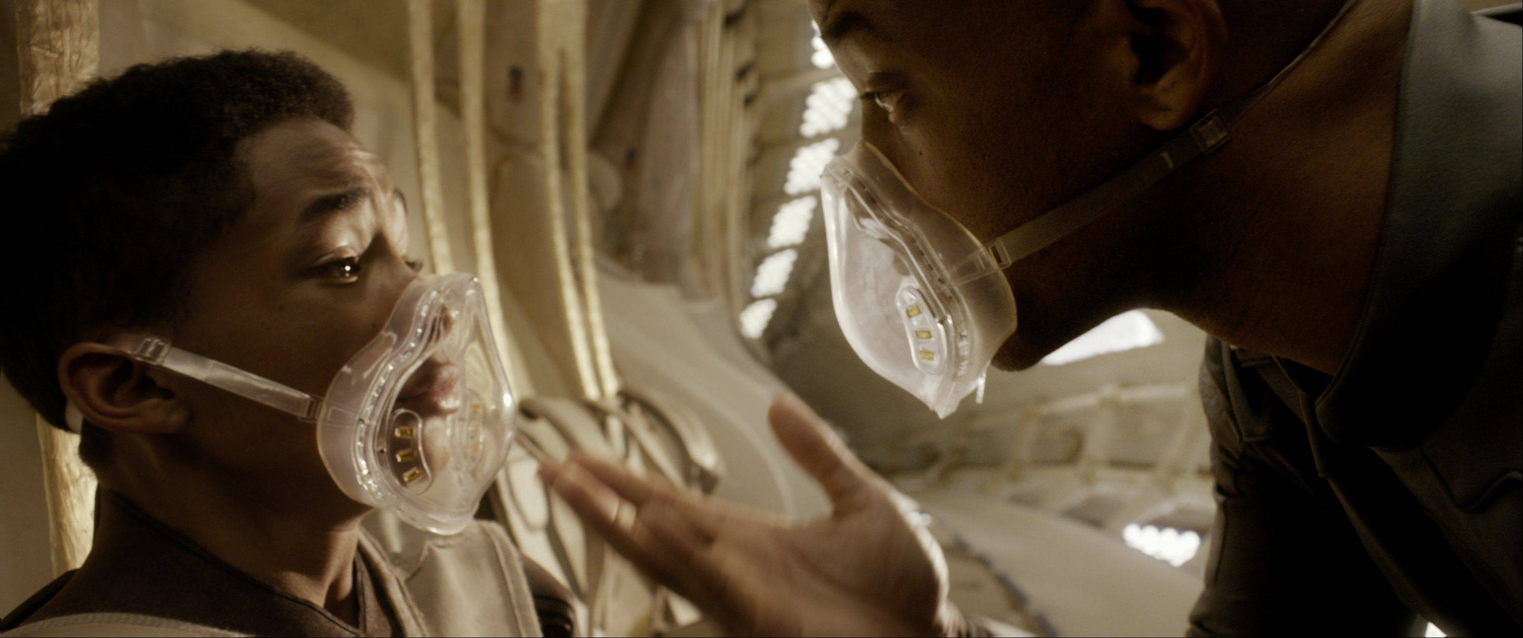 "A wannabe space ranger (Jaden Smith) is reassured by his commander father (Will Smith) during a crash landing in ""After Earth."""
