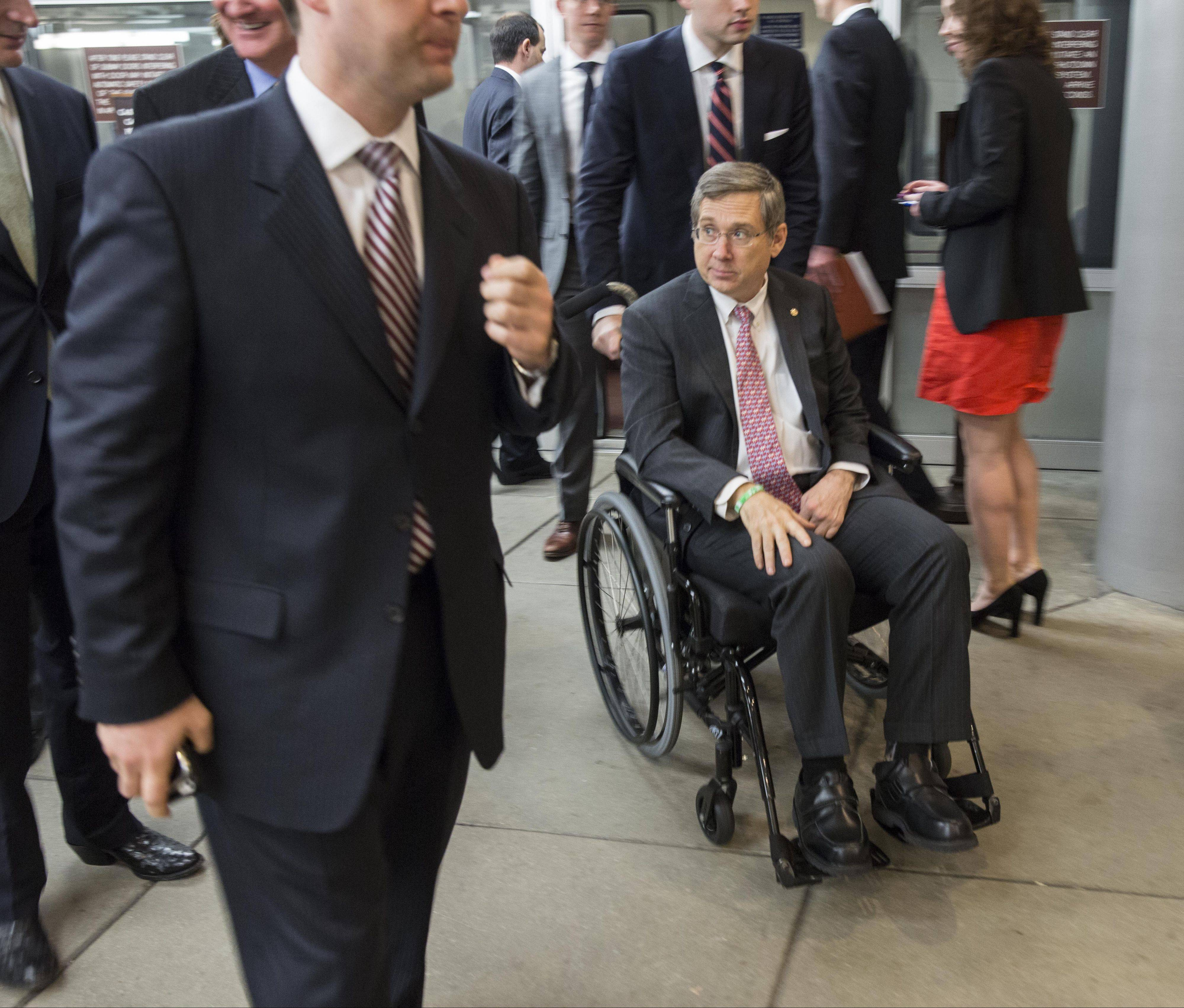 U.S. Sen. Mark Kirk, who travels around the Capitol by wheelchair since his return to Congress after suffering a stroke, heads from his office to the Senate for a vote.