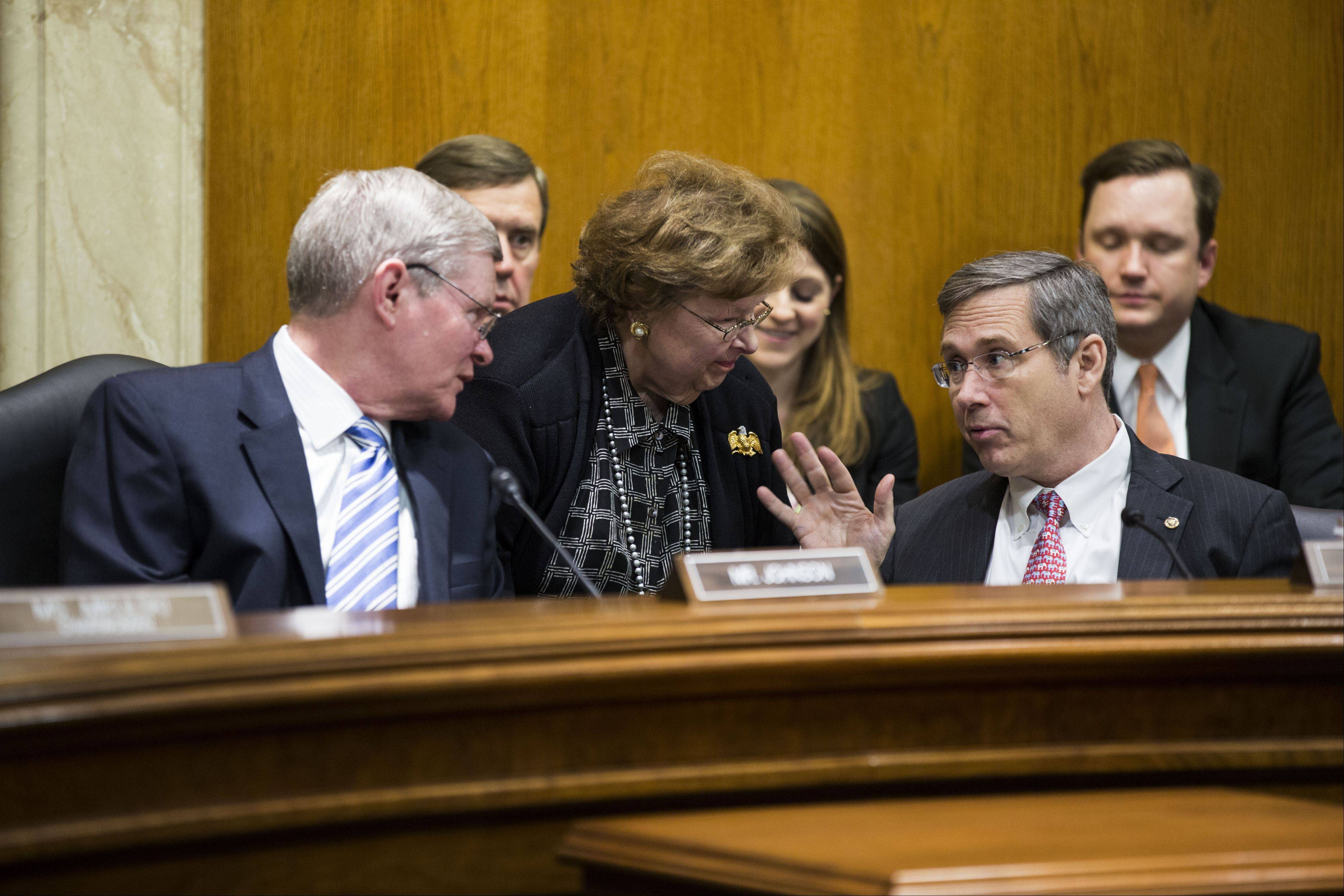 U.S. senators Mark Kirk, a Highland Park Republican at front right, and Tim Johnson, a South Dakota Democrat at left, speak with others after a Military Construction, Veteran Affairs, and Related Agencies Subcommittee hearing in Washington, D.C. Both senators returned to Congress after suffering strokes.