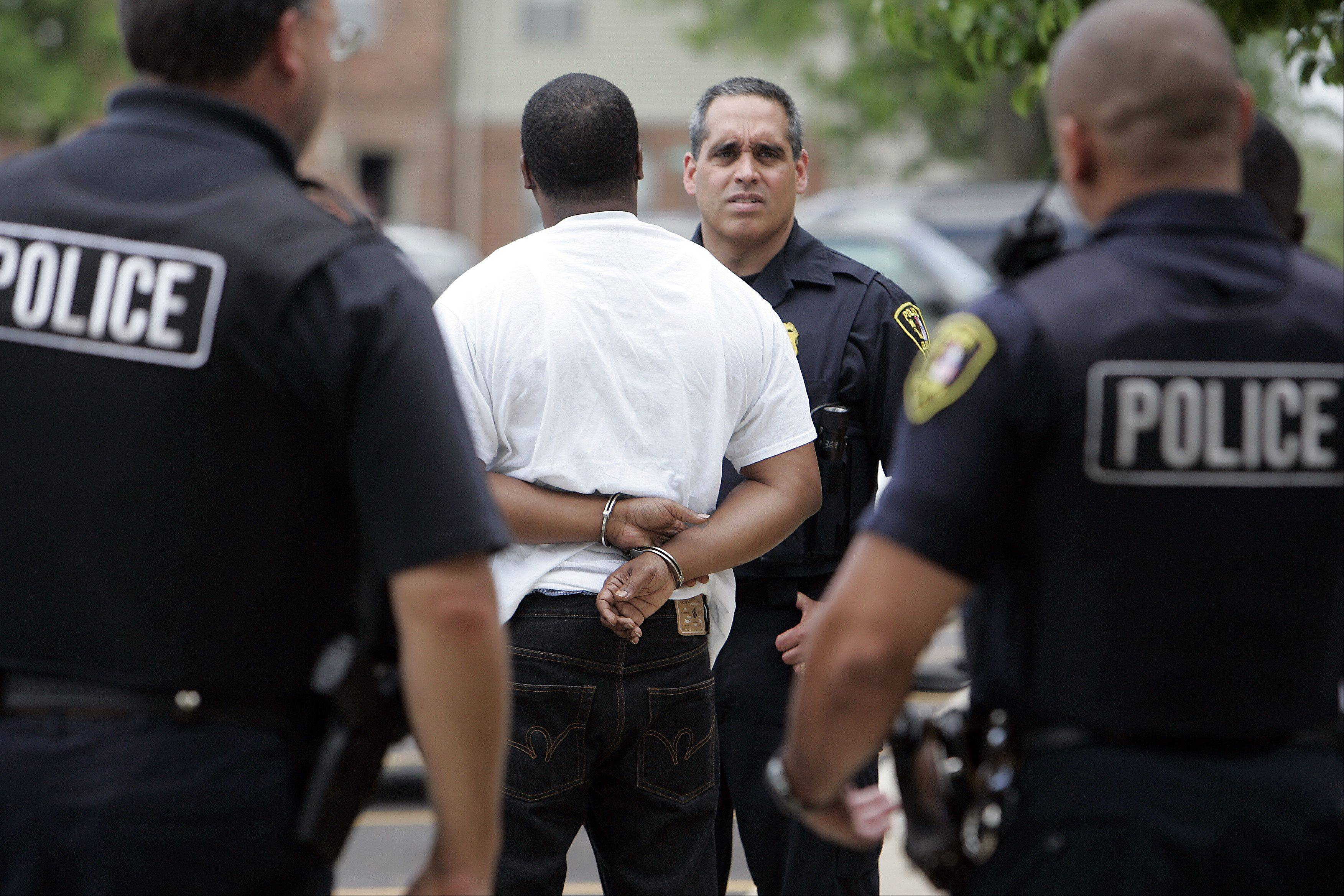 Elgin Police Sgt. Rick Santiago questions a suspect Thursday during a drug sweep.