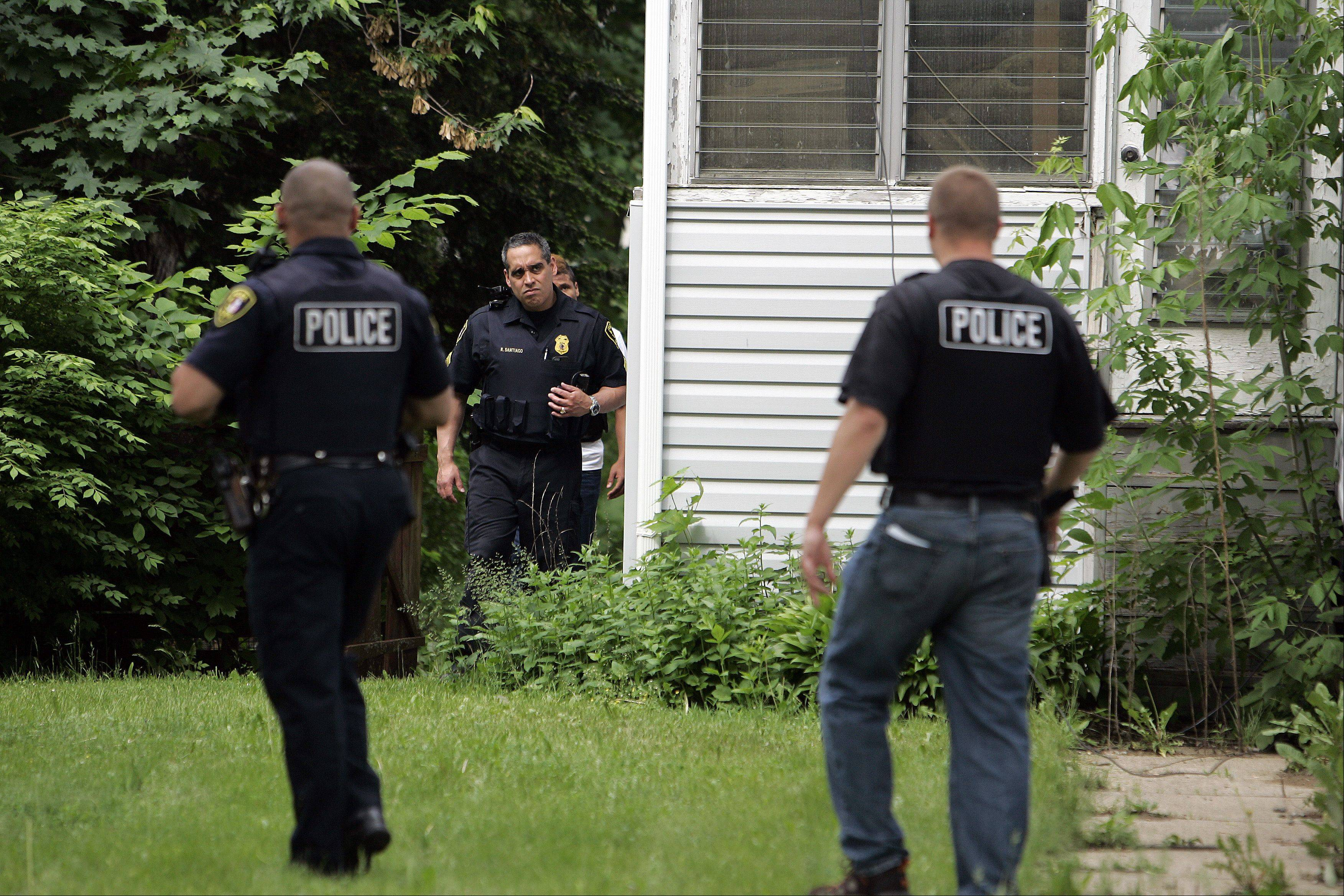 Elgin Police Sgt. Rick Santiago, center, works his way around a house during a drug sweep conducted Thursday. About 80 people with charges related to drug sales were targeted in the yearlong investigation.