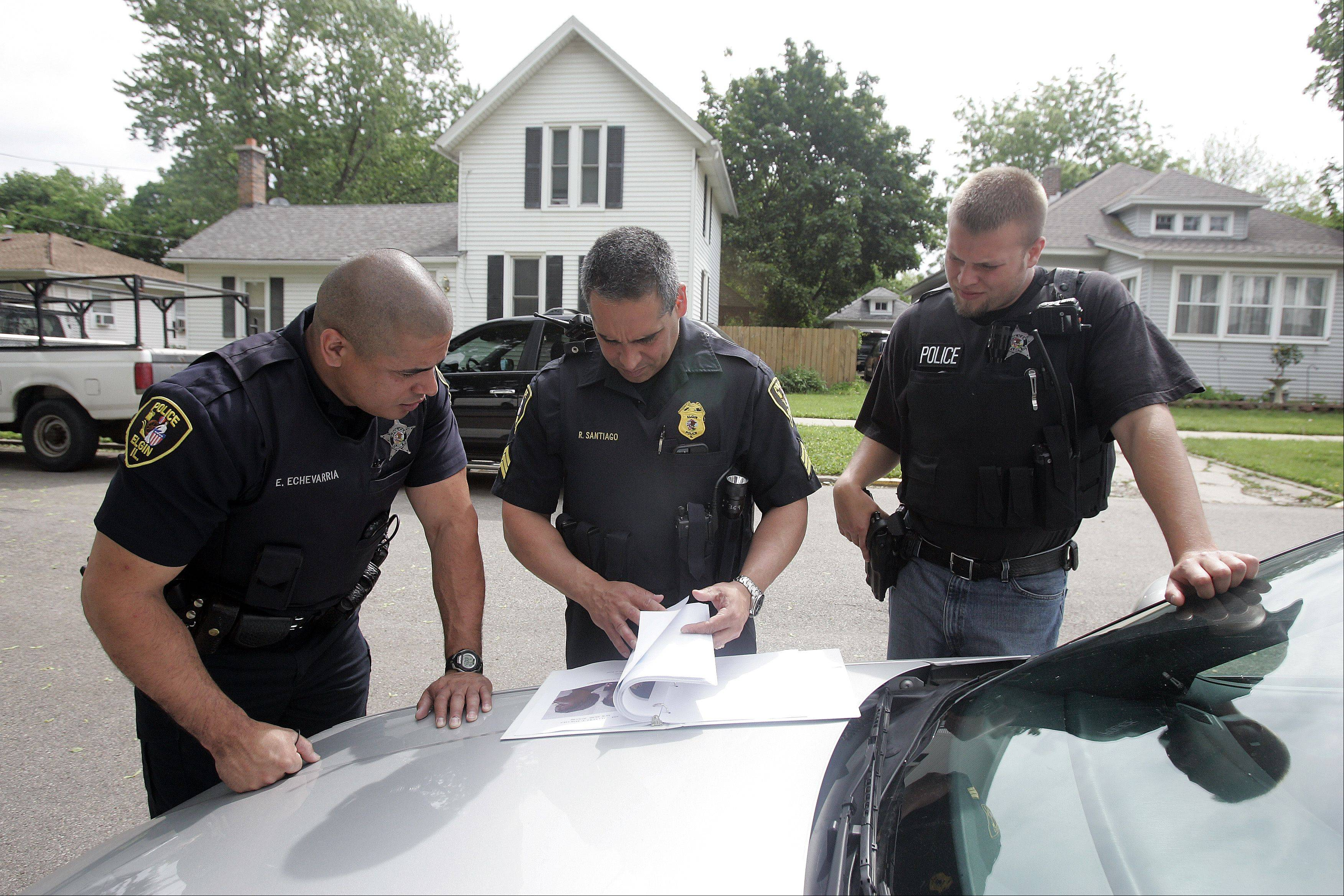 Elgin Police Officer Eric Echevarria, from left, Sgt. Rick Santiago and Officer Will Yucaitis plan their route before a drug sweep Thursday. The yearlong investigation targeted about 80 people with charges related to drug sales, police said.