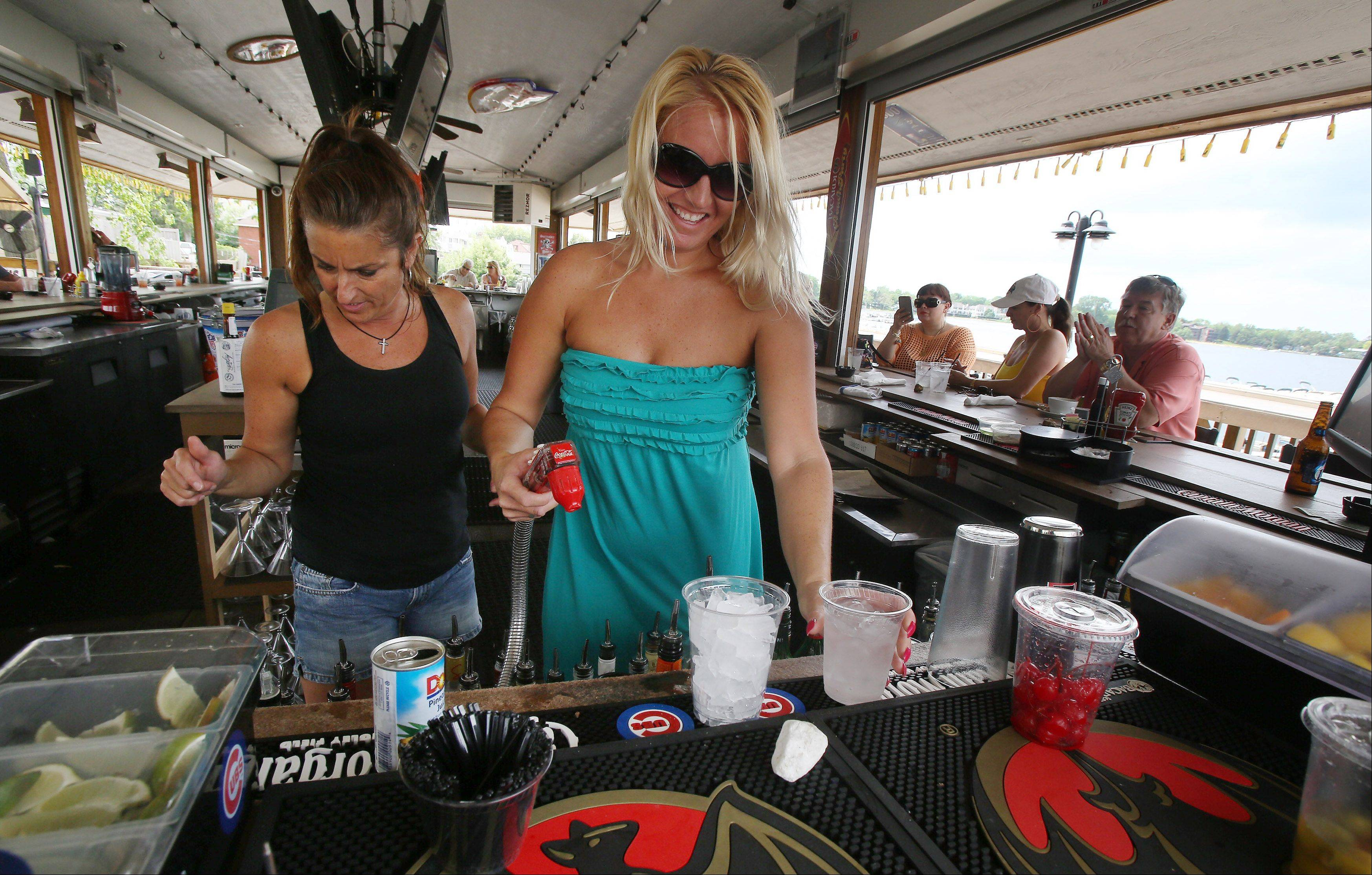 Bartender Lisa Simpson, left, and general manager Jennifer Hansen work in the outdoor bar at Docks Bar and Grill in Wauconda. The village is working with the restaurant/bar and other entertainment establishments in the town to limit noise.