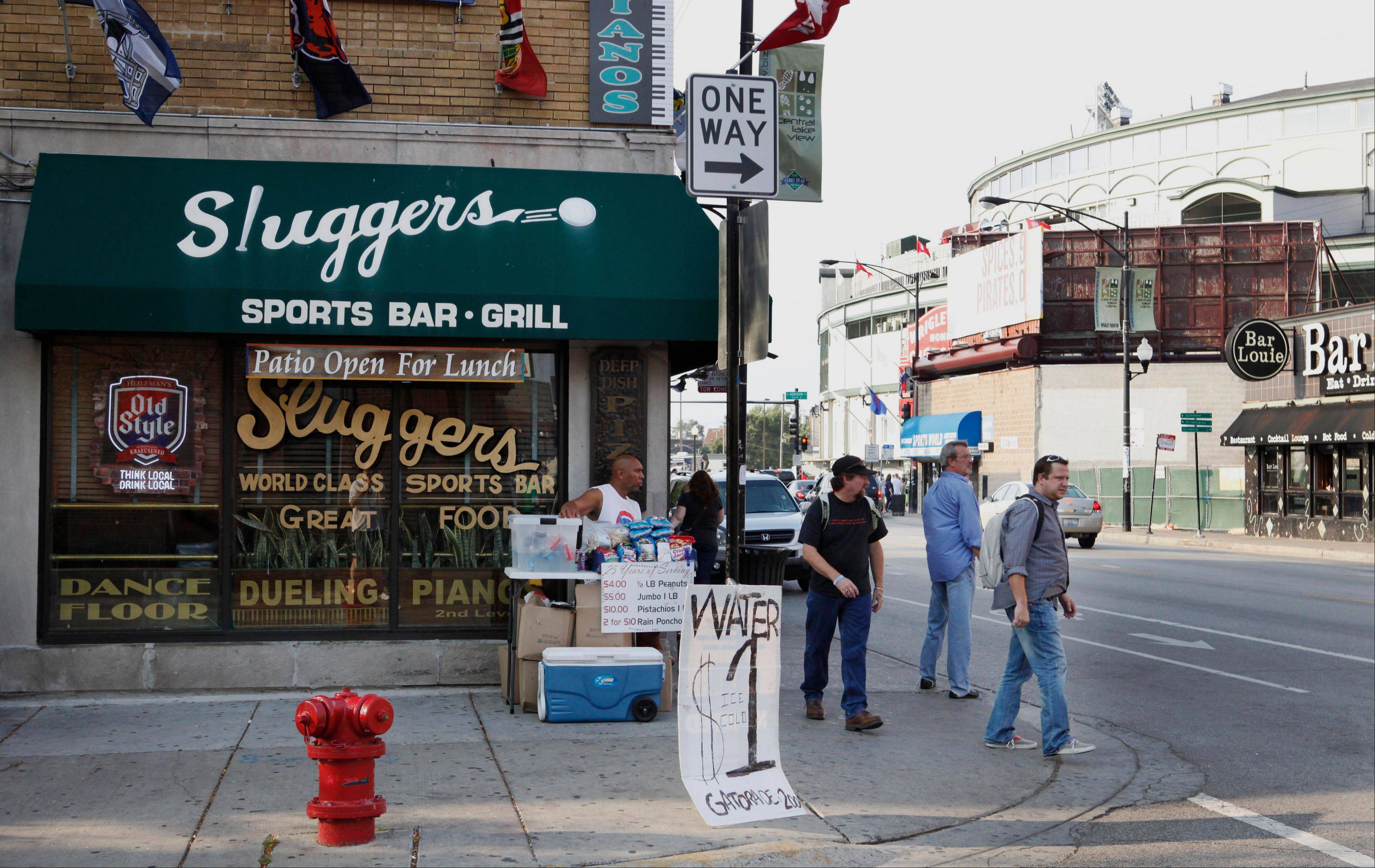 This 2010 file photo shows Sluggers Sports Bar and Grill near Wrigley Field, background, before a Chicago Cubs baseball game in Chicago.