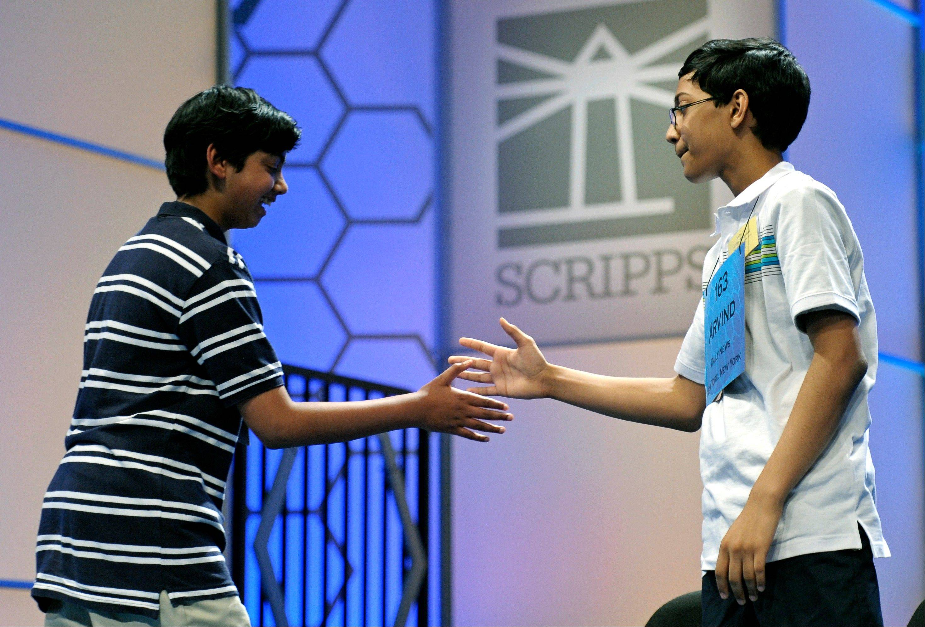 Scripps National Spelling Bee champion Arvind Mahankali, 13, of Bayside Hills, N.Y. extends his hand to second place finisher Pranav Sivakumar, 13, Tower Lakes, Ill., after Sivakumar incorrectly spelled his final word during the finals in Oxon Hill, Md.