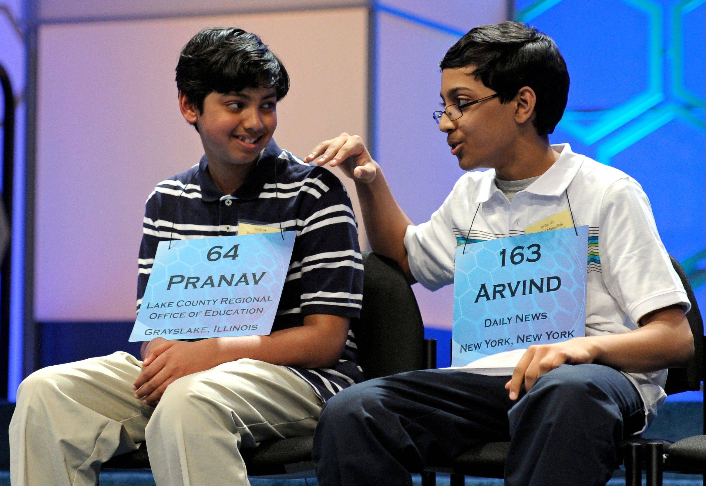 Scripps National Spelling Bee champion Arvind Mahankali, 13, of Bayside Hills, N.Y., pats second-place finisher Pranav Sivakumar, 13, of Tower Lakes on the shoulder after Sivakumar incorrectly spelled his final word during the finals in Oxon Hill, Md.