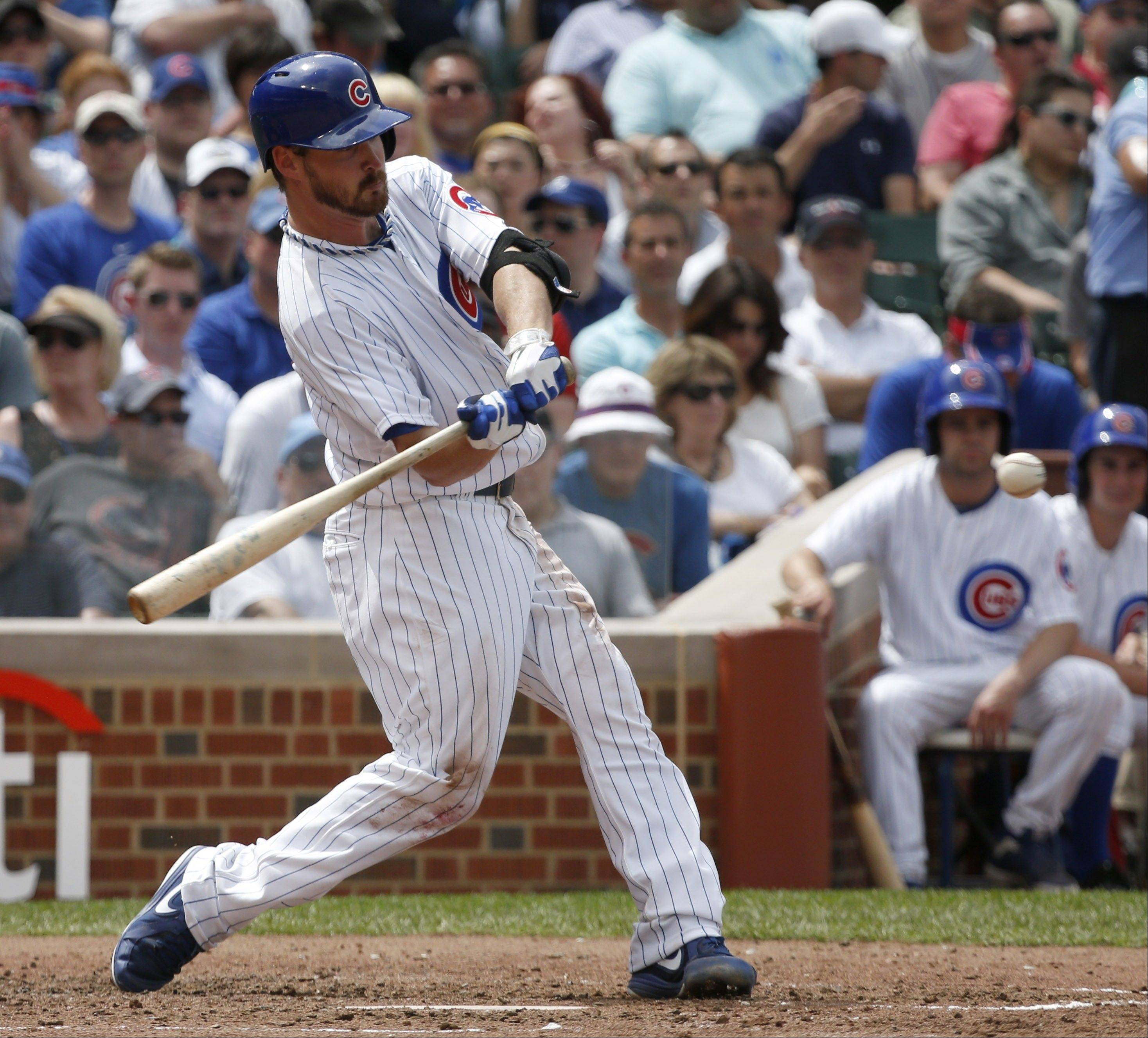 Chicago Cubs' Travis Wood hits a grand slam off Chicago White Sox starting pitcher Jake Peavy during the fourth inning of an interleague baseball game Thursday, May 30, 2013, in Chicago. The Cubs Darwin Barney, Luis Valbuena, and Welington Castillo also scored on the hit.