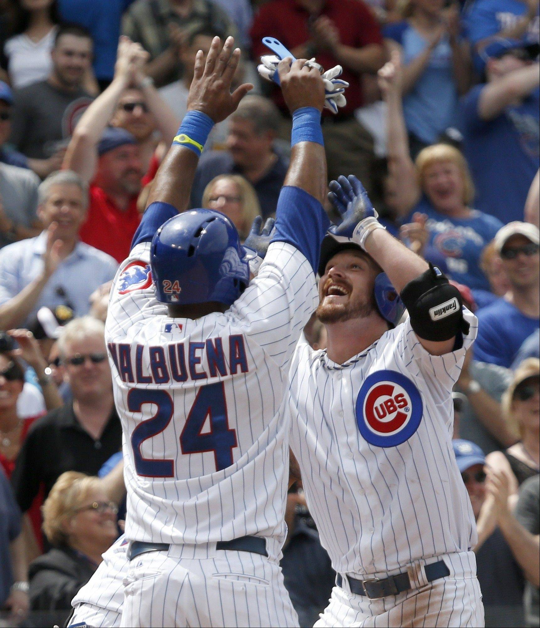 Chicago Cubs' Travis Wood, right, celebrates at home plate with Luis Valbuena after hitting a grand slam off Chicago White Sox starting pitcher Jake Peavy during the fourth inning of an interleague baseball game Thursday, May 30, 2013, in Chicago. The Cubs' Darwin Barney and Welington Castillo also scored on the hit.
