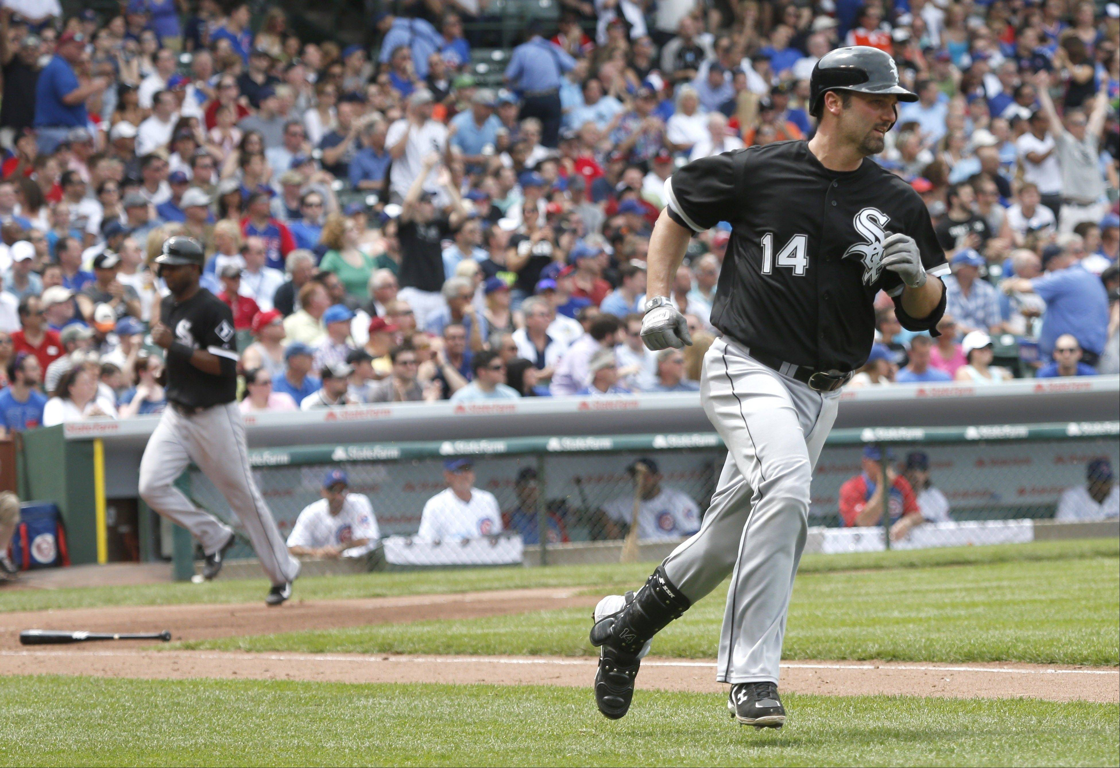 Chicago White Sox's Paul Konerko (14) heads to first after hitting an RBI single off Chicago Cubs starting pitcher Travis Wood, scoring Alejandro De Aza, left, during the third inning of an interleague baseball game Thursday, May 30, 2013, in Chicago.