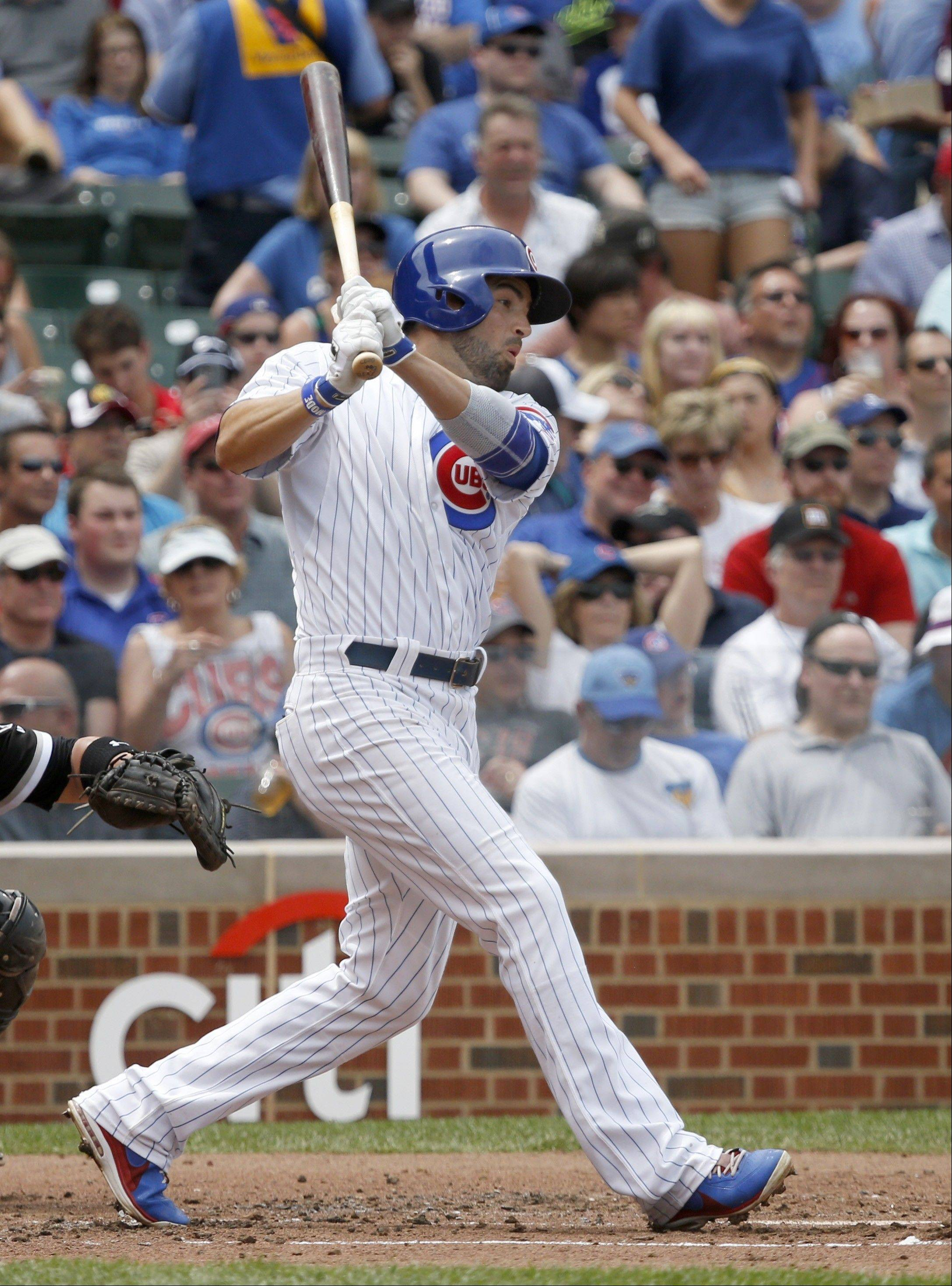 Chicago Cubs' David DeJesus hits an RBI single off Chicago White Sox starting pitcher Jake Peavy, scoring Darwin Barney, during the second inning of an interleague baseball game Thursday, May 30, 2013, in Chicago.